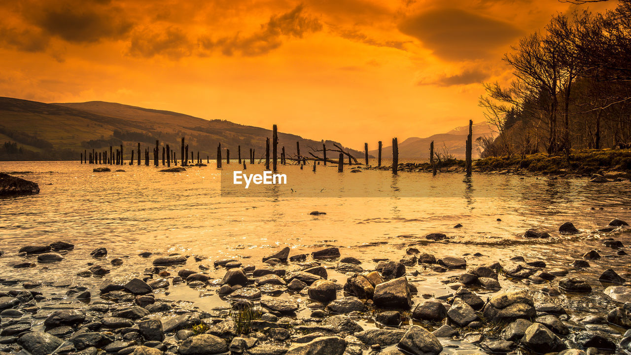 sky, sunset, water, cloud - sky, beauty in nature, scenics - nature, tranquility, tranquil scene, nature, orange color, no people, rock, sea, solid, beach, land, rock - object, mountain, idyllic, outdoors