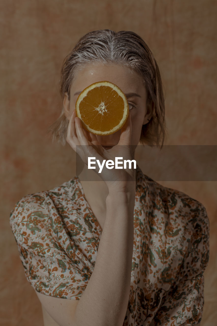 one person, holding, healthy eating, food and drink, fruit, indoors, citrus fruit, food, wellbeing, women, adult, real people, lifestyles, freshness, cross section, front view, leisure activity, focus on foreground, orange, hairstyle, floral pattern