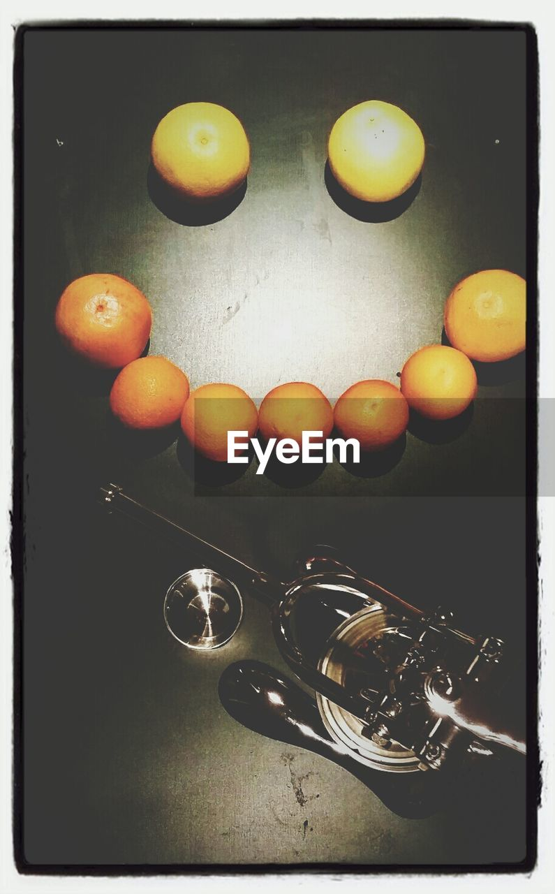 High Angle View Of Lemons Arranged As Face By Kitchen Utensils On Table
