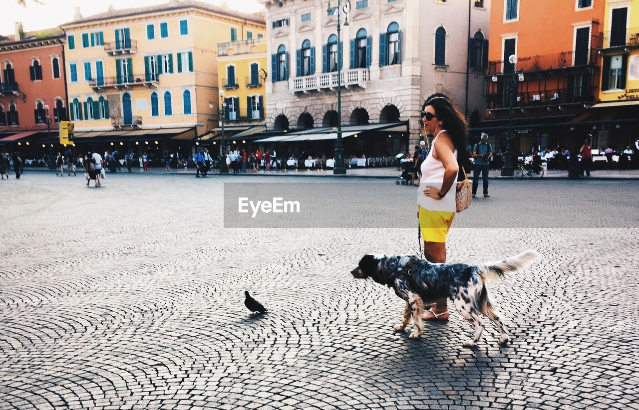 real people, building exterior, one person, built structure, architecture, full length, casual clothing, walking, incidental people, street, lifestyles, leisure activity, women, outdoors, pets, young adult, young women, day, dog, domestic animals, city, mammal, adult, adults only, people
