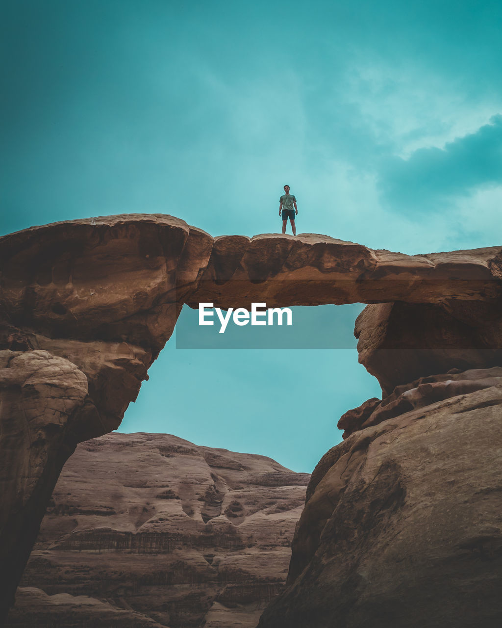rock, rock - object, sky, solid, rock formation, real people, lifestyles, leisure activity, nature, low angle view, one person, standing, day, beauty in nature, adventure, physical geography, activity, men, scenics - nature, outdoors, eroded