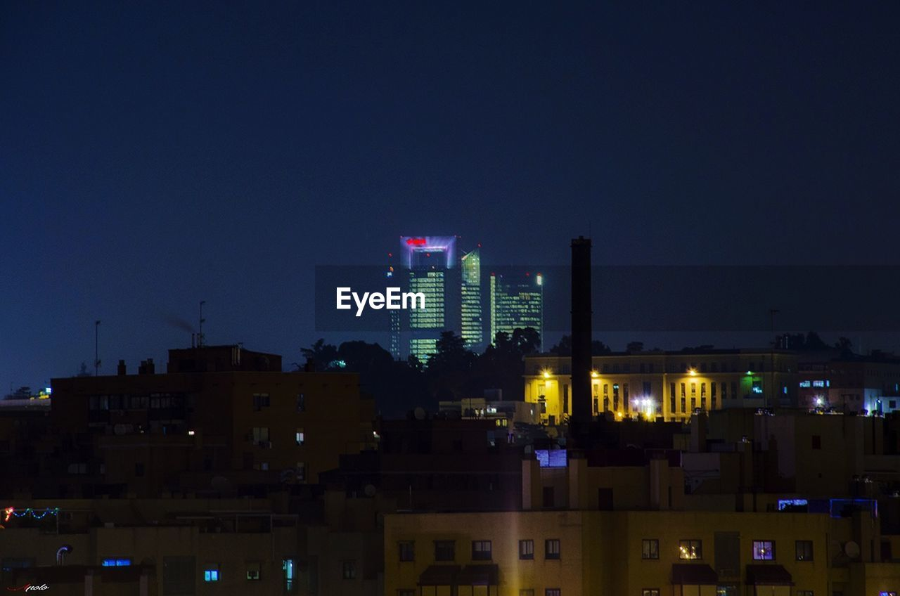 architecture, building exterior, built structure, illuminated, city, cityscape, skyscraper, night, modern, development, no people, architectural style, sky, tall, outdoors, growth, clear sky, urban skyline