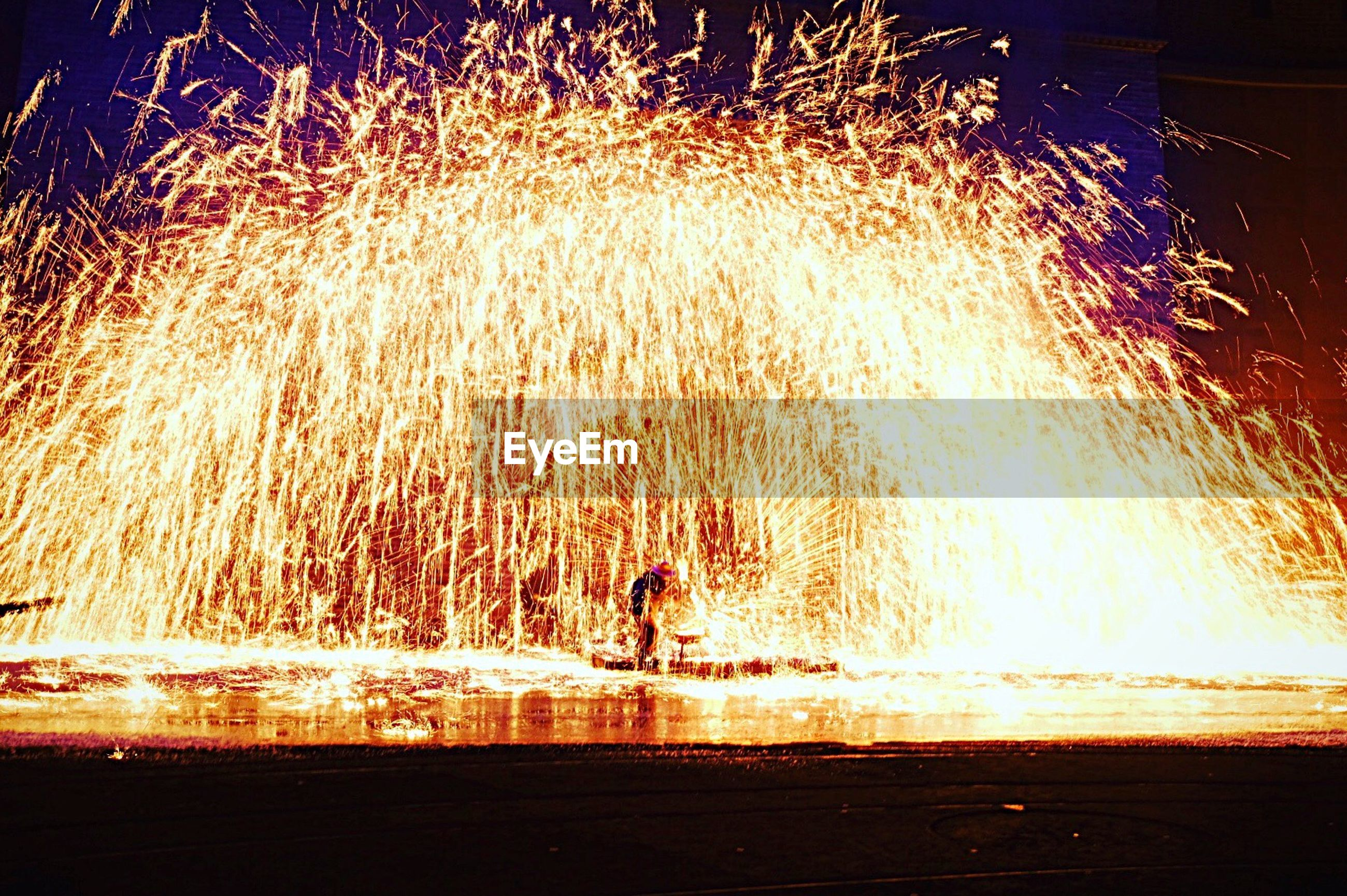 motion, night, celebration, heat - temperature, sparks, outdoors, firework display, illuminated, blurred motion, long exposure, exploding, firework - man made object, event, burning, one person, firework, wire wool, people