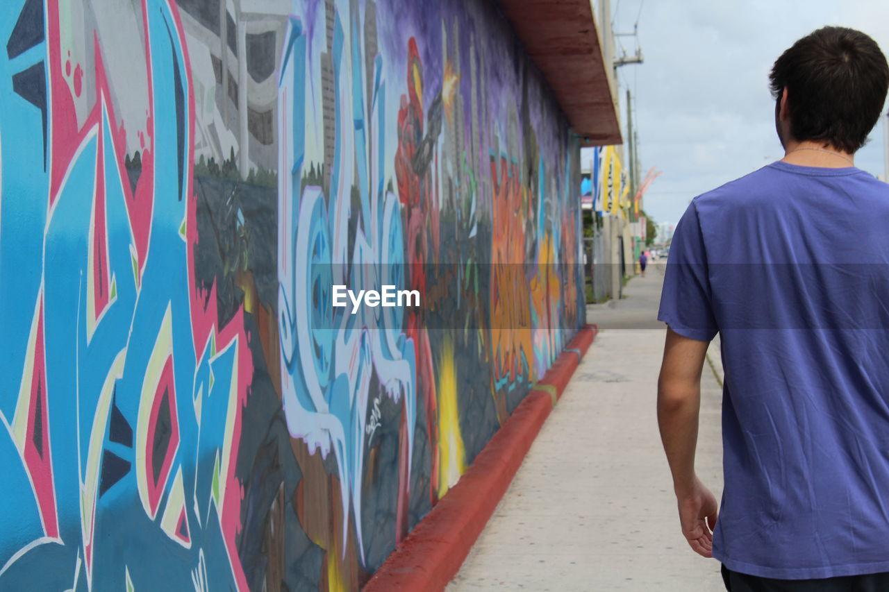 Rear View Of Man Walking By Graffiti Wall On Sidewalk