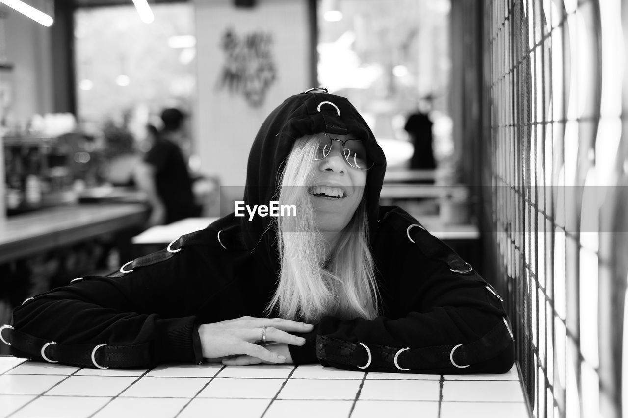 Cheerful Young Woman Wearing Hooded Shirt Sitting At Restaurant