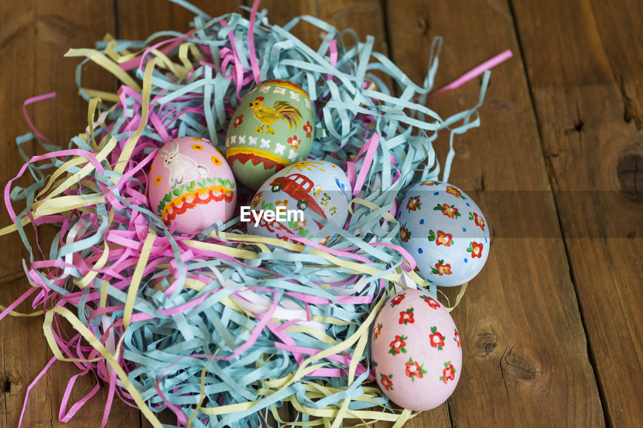 indoors, still life, multi colored, table, high angle view, no people, celebration, food, food and drink, pattern, close-up, wood - material, holiday, focus on foreground, container, easter, easter egg, ribbon, decoration, temptation, floral pattern