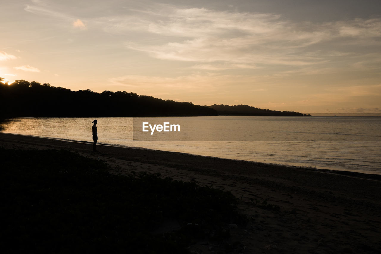 SILHOUETTE OF PEOPLE ON BEACH AGAINST SKY