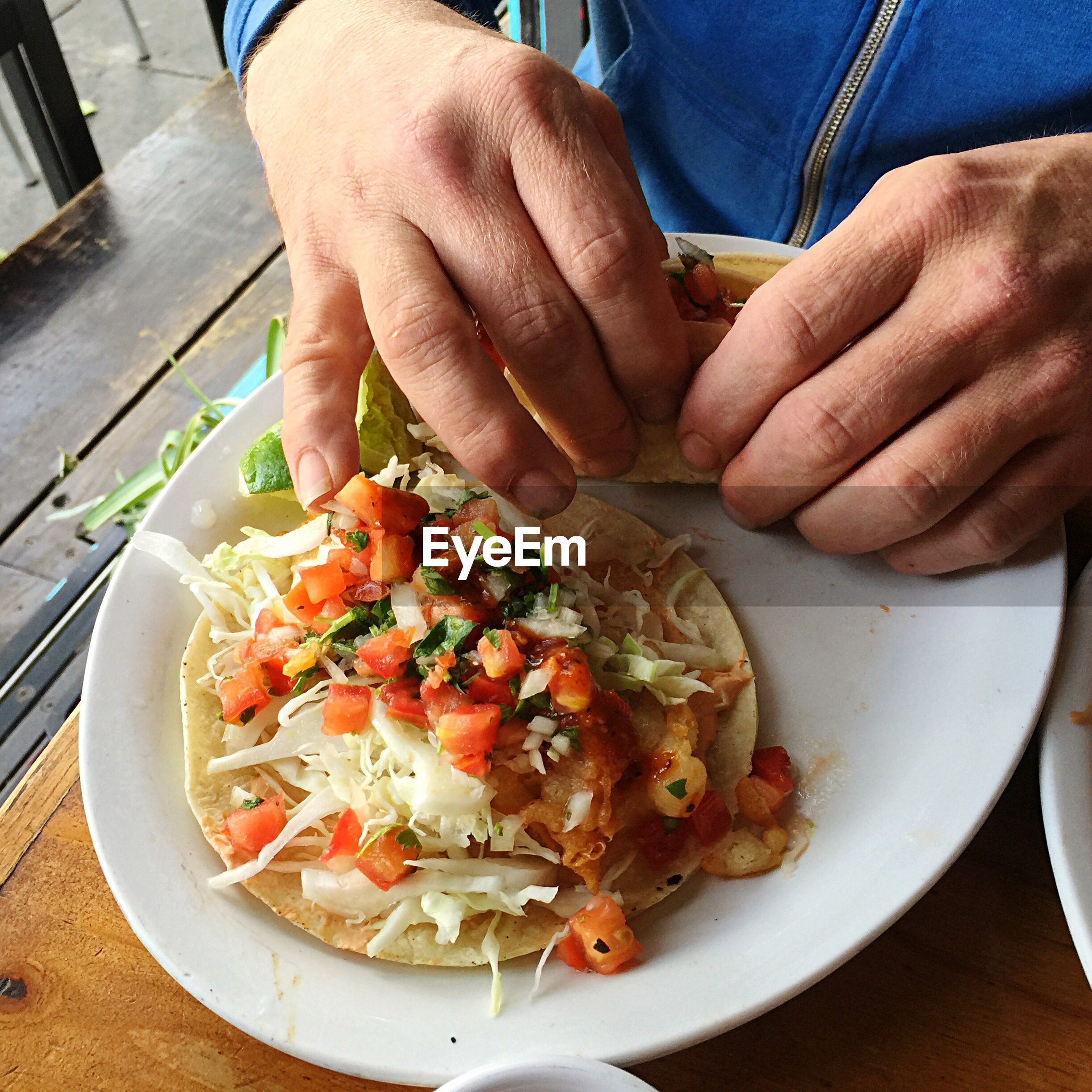 Cropped image of person holding food