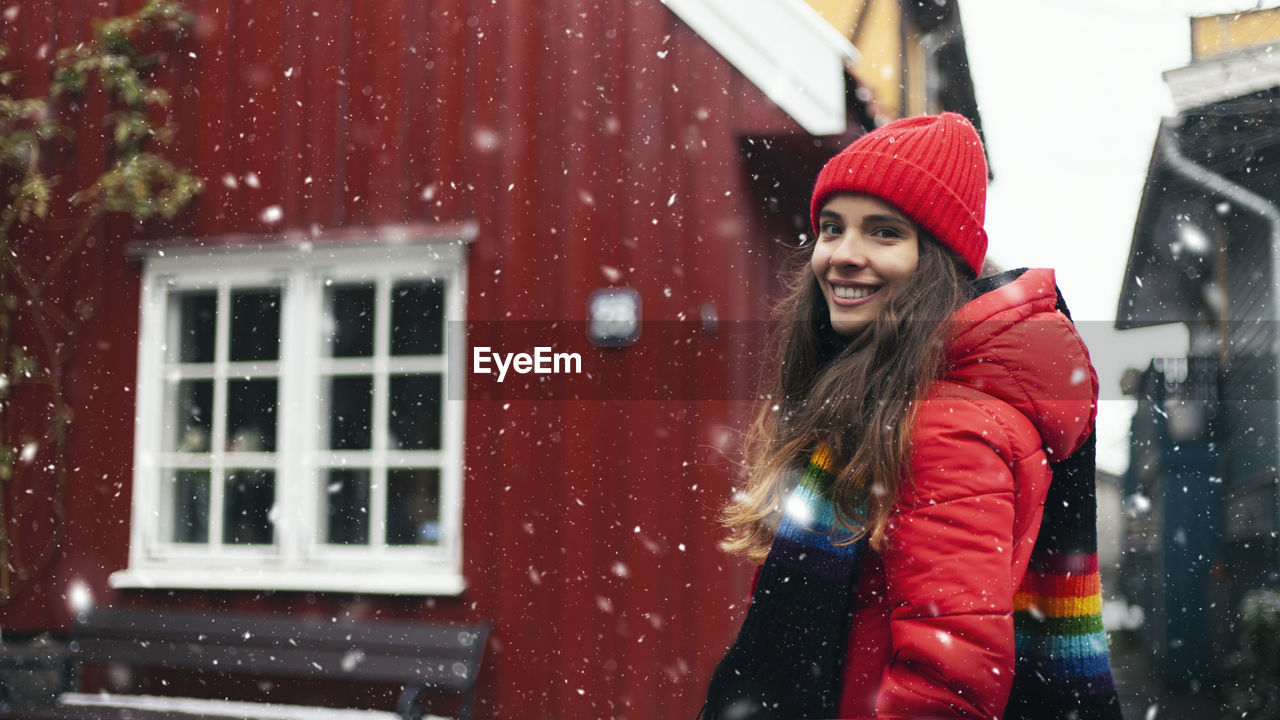 Portrait of smiling woman standing outside house during winter