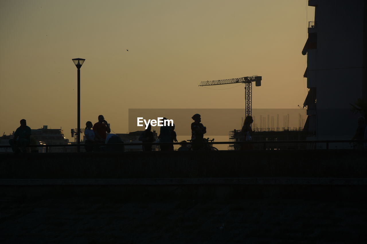 SILHOUETTE PEOPLE AGAINST CLEAR SKY AT SUNSET