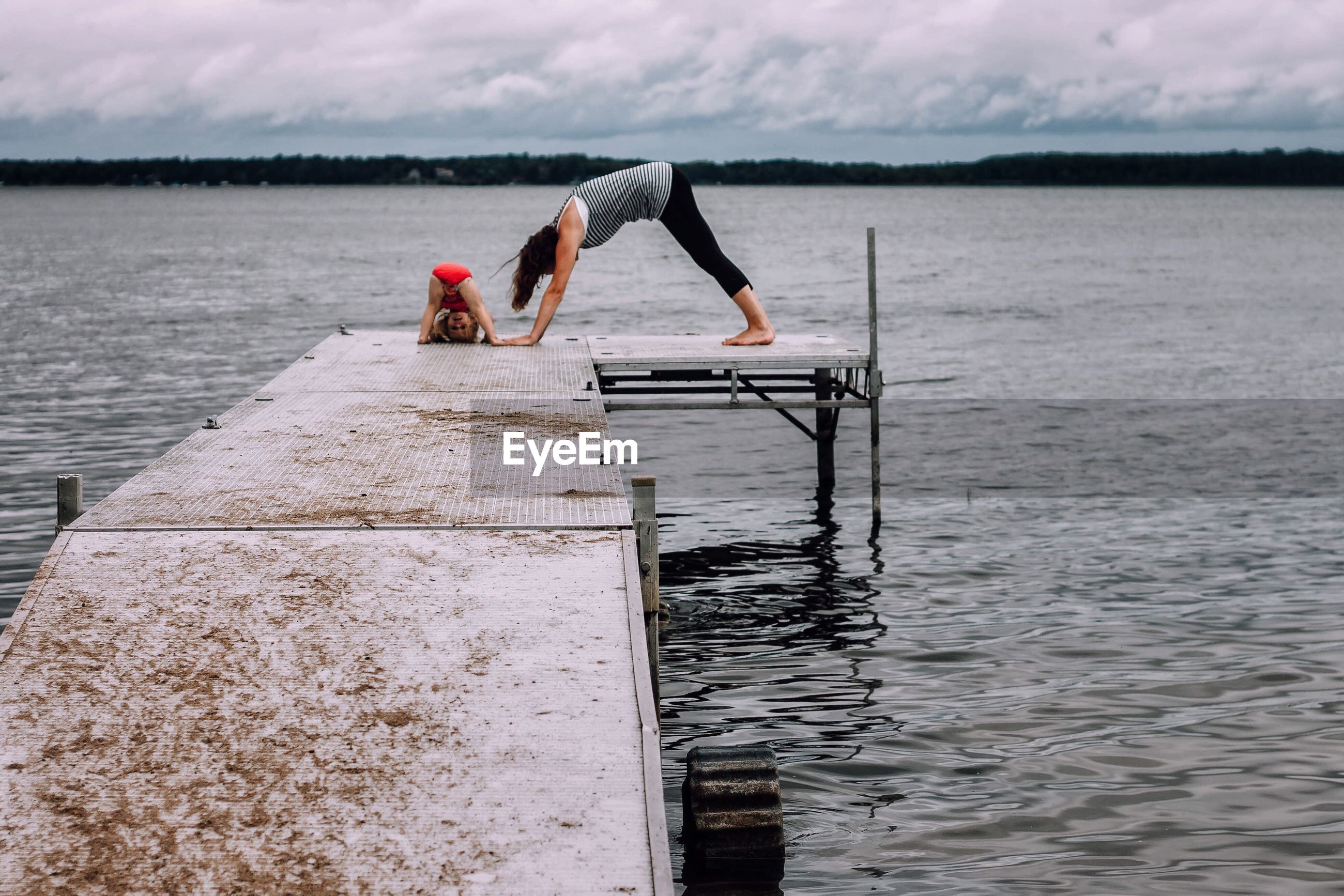 Young woman with daughter doing yoga on pier over lake