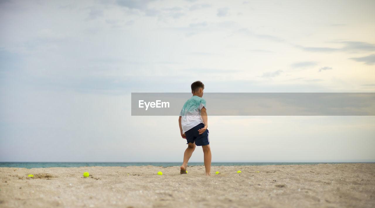 Boy teenager exercising on the sandy beach. physical training. tennis balls.