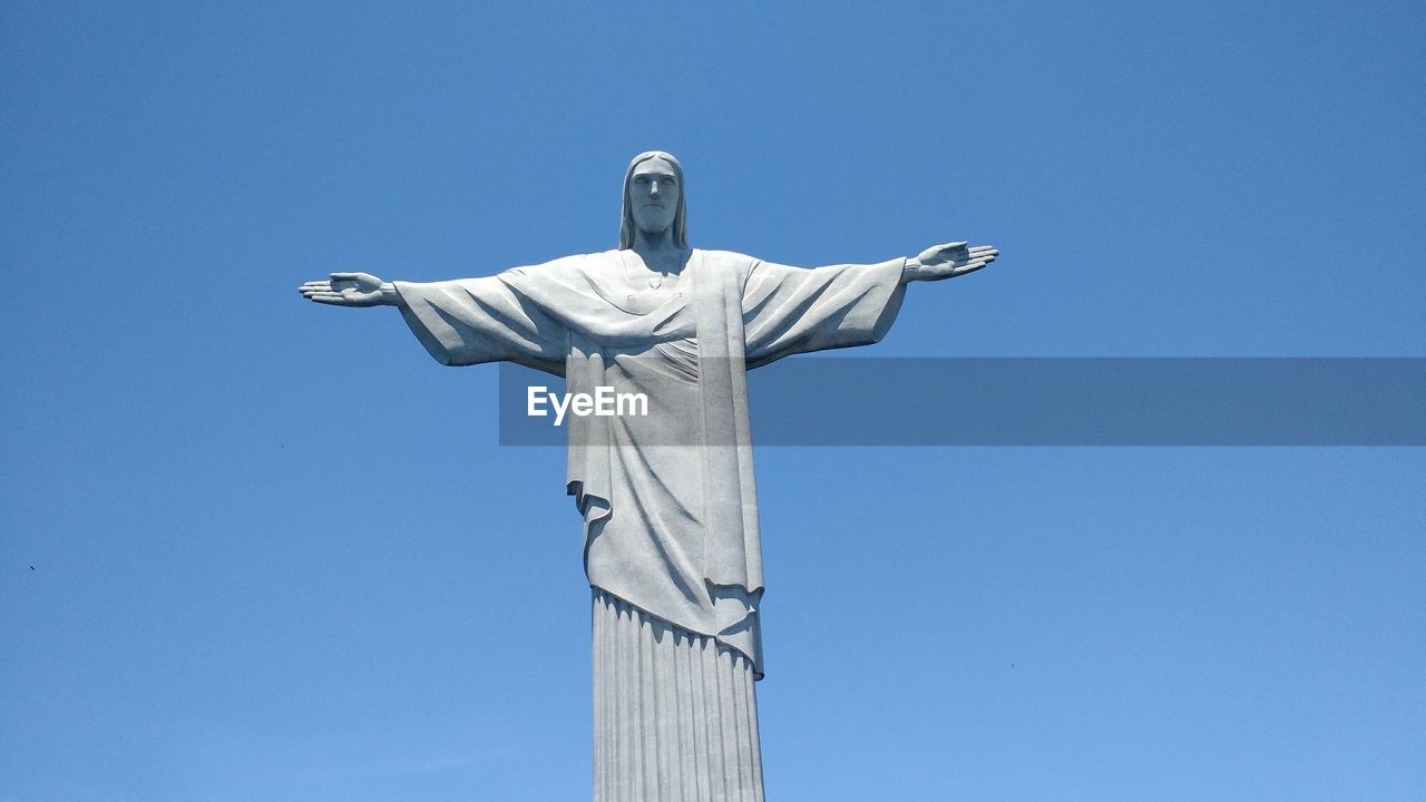 Low angle view of christ the redeemer statue against clear blue sky