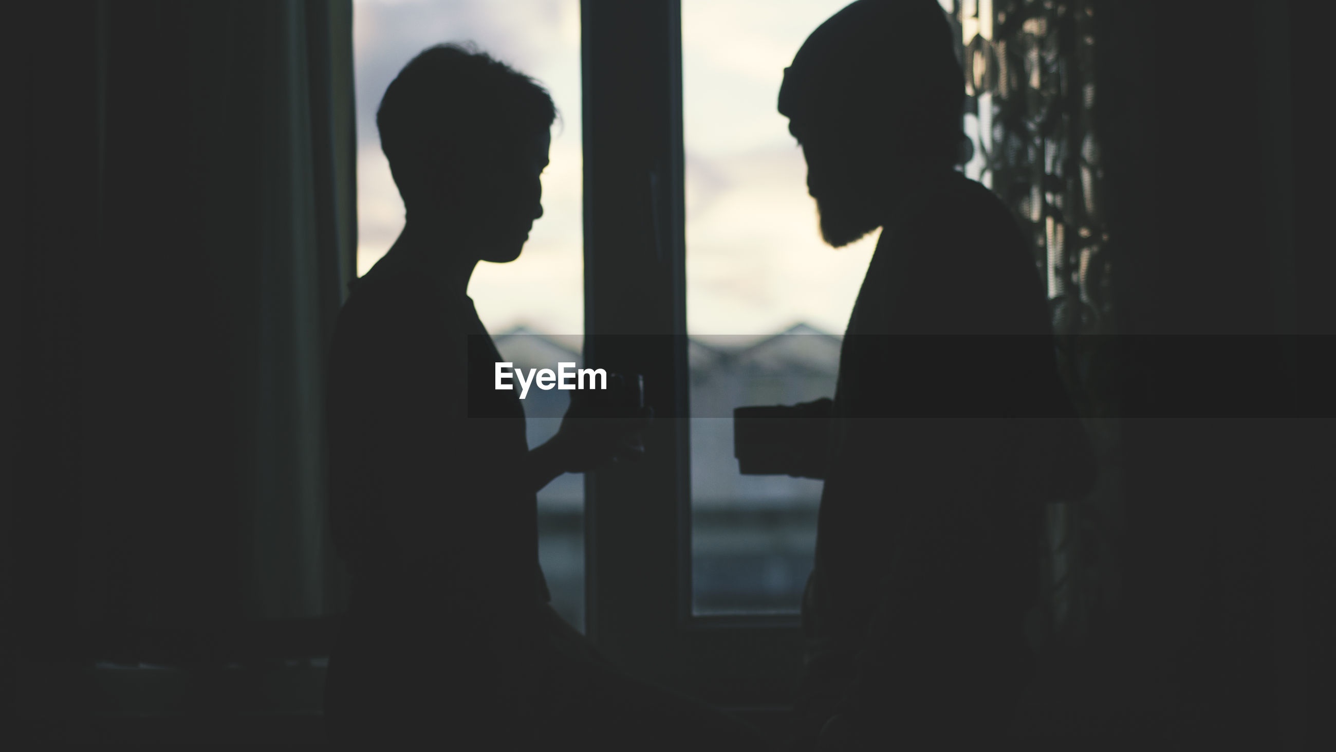 Silhouette couple standing by window
