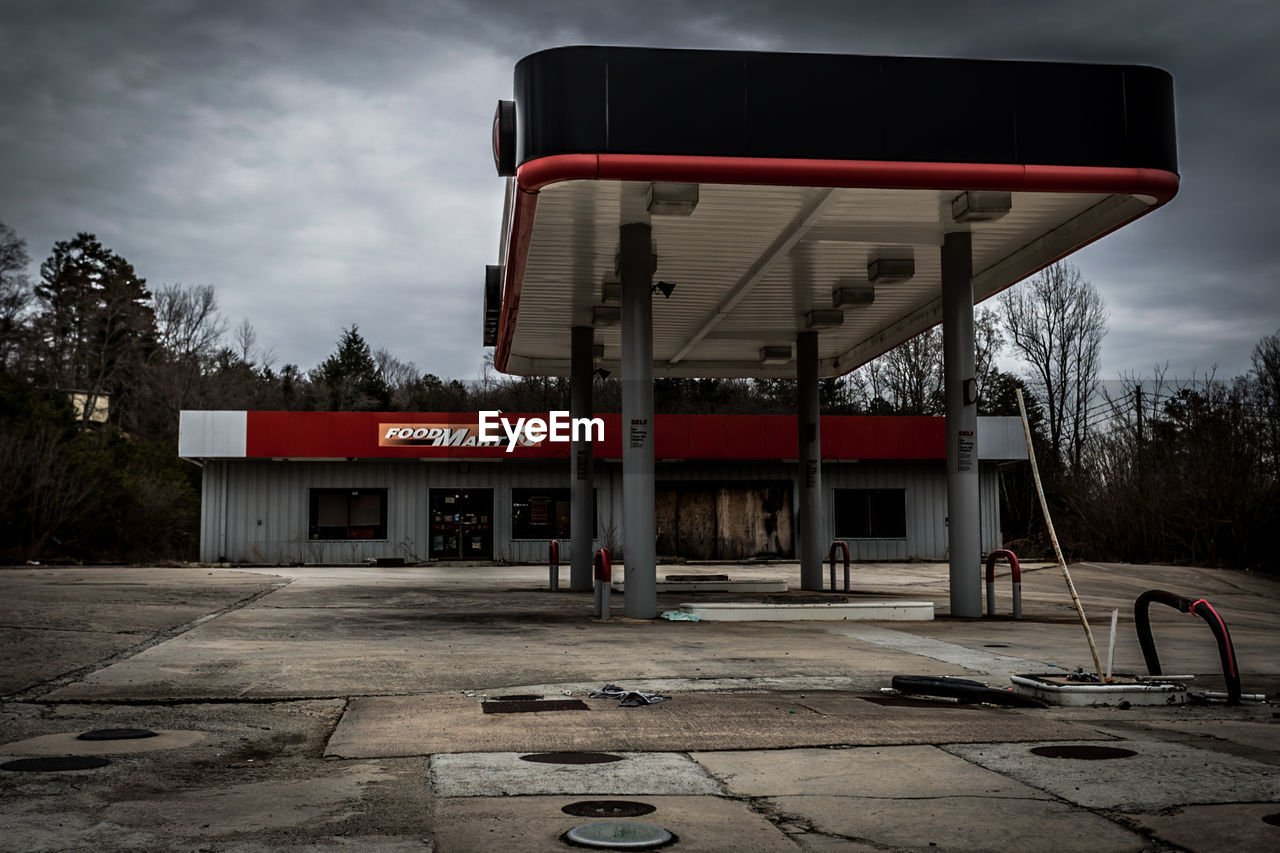 gas station, built structure, building exterior, fuel pump, sky, outdoors, architecture, no people, abandoned, tree, day, basketball hoop, parking garage