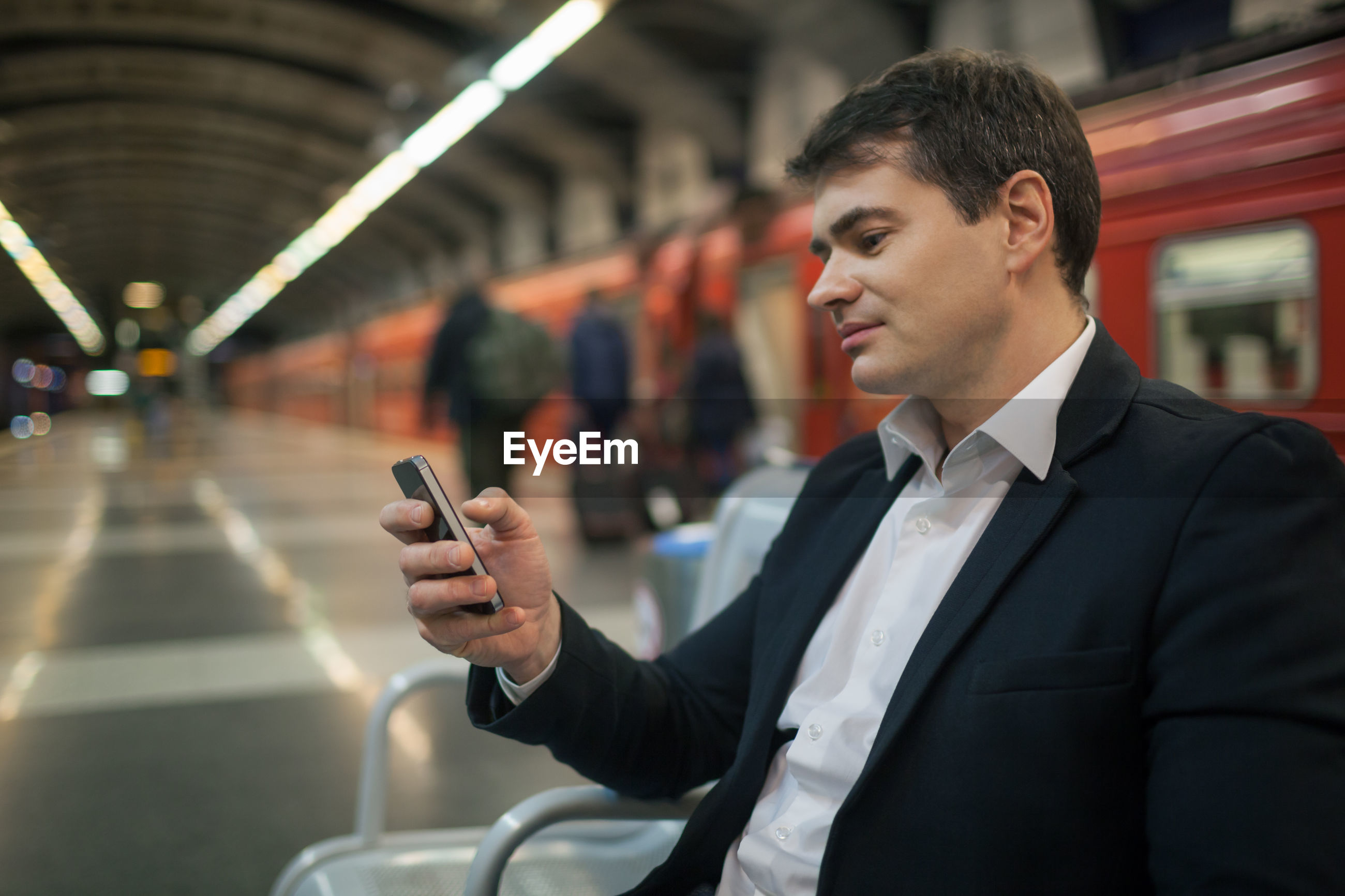 Businessman using mobile phone while sitting at subway station