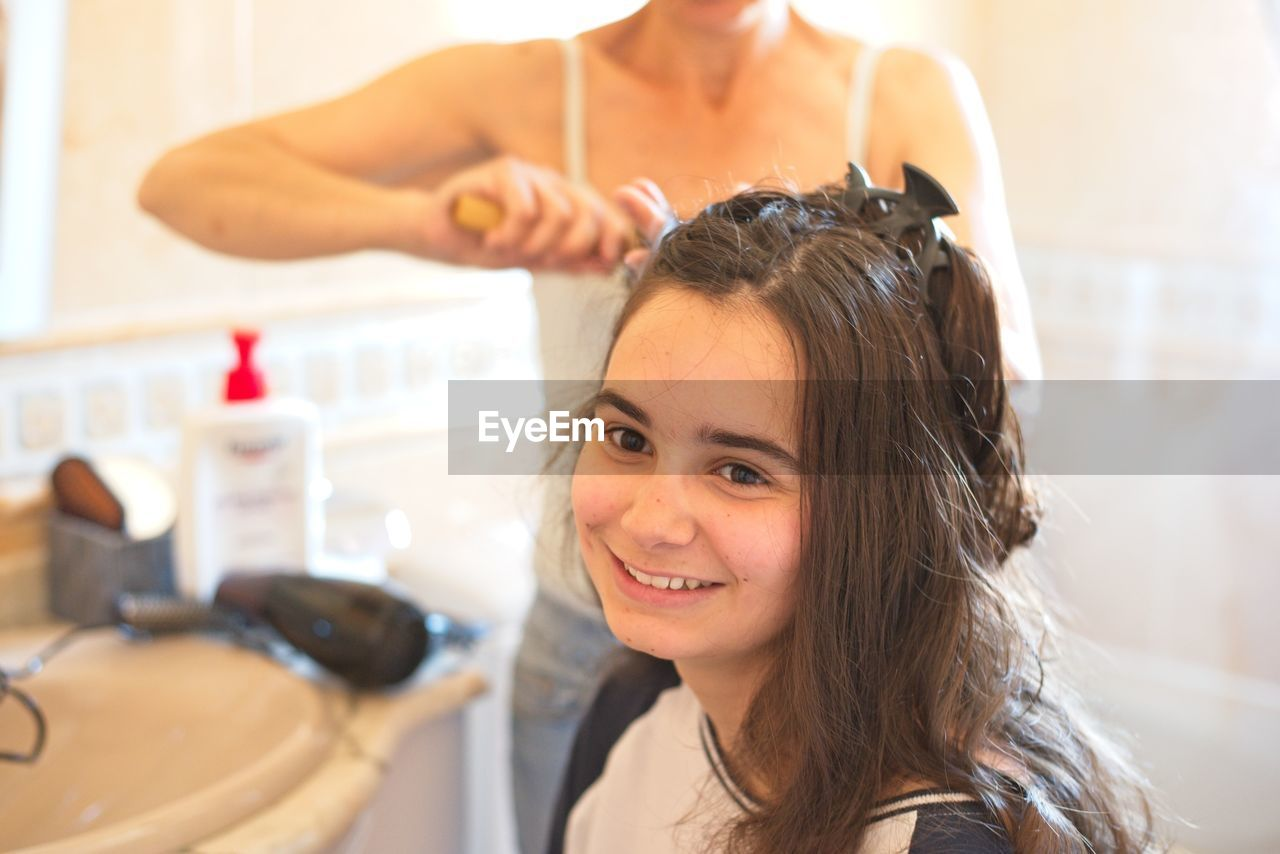 Midsection of hairdresser combing young woman hair in salon