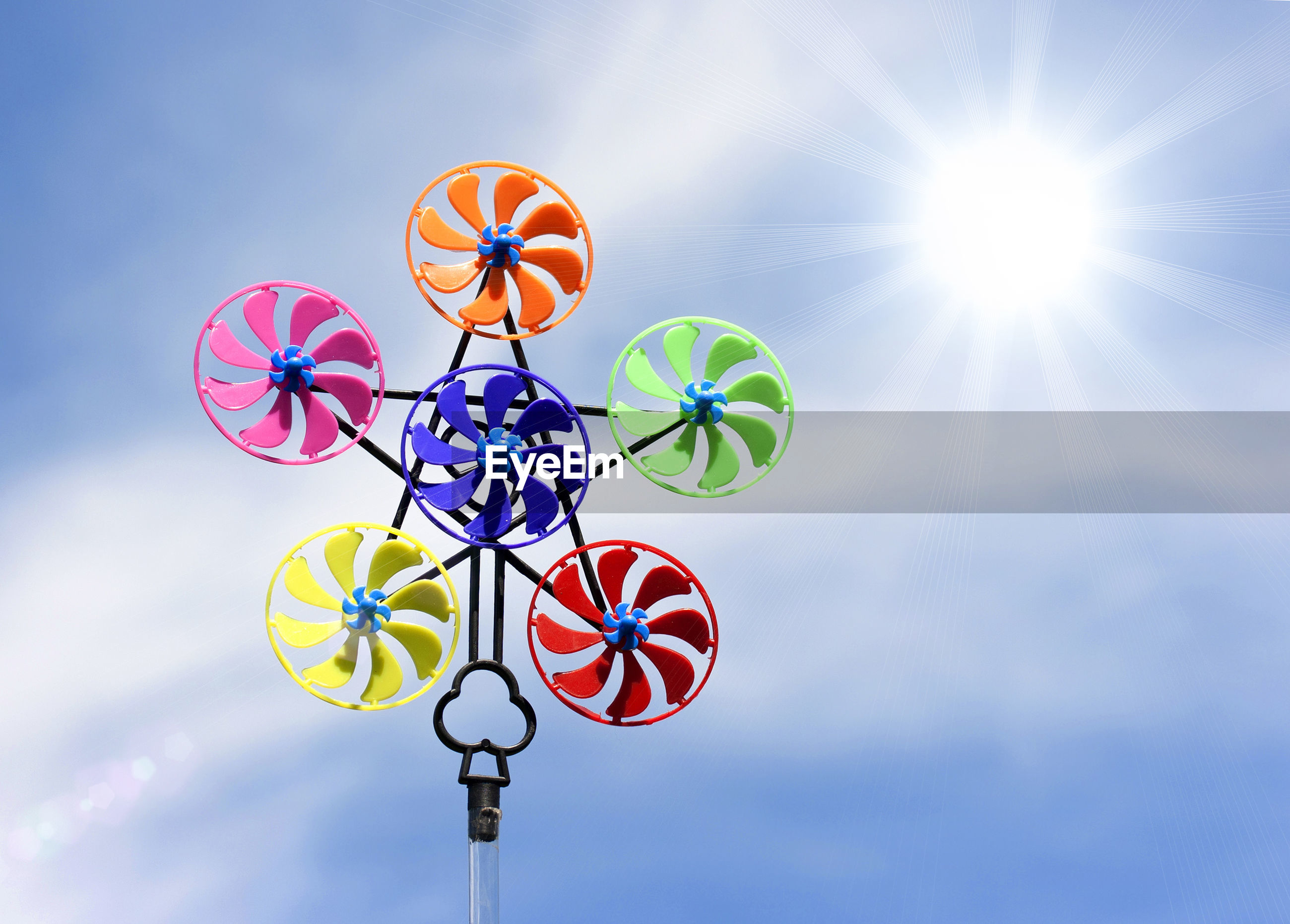 Low angle view of colorful pinwheel toy against sky during sunny day