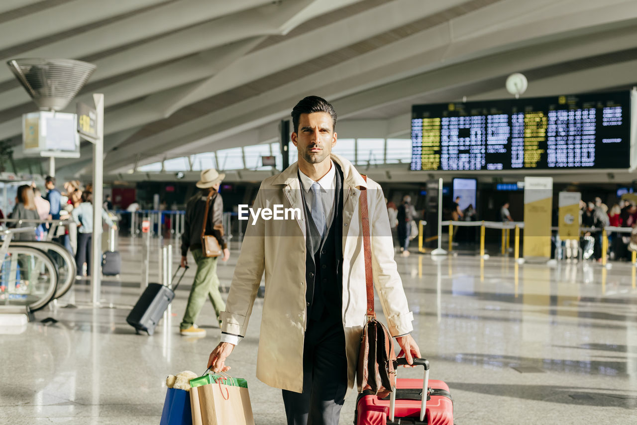 MEN STANDING IN AIRPORT