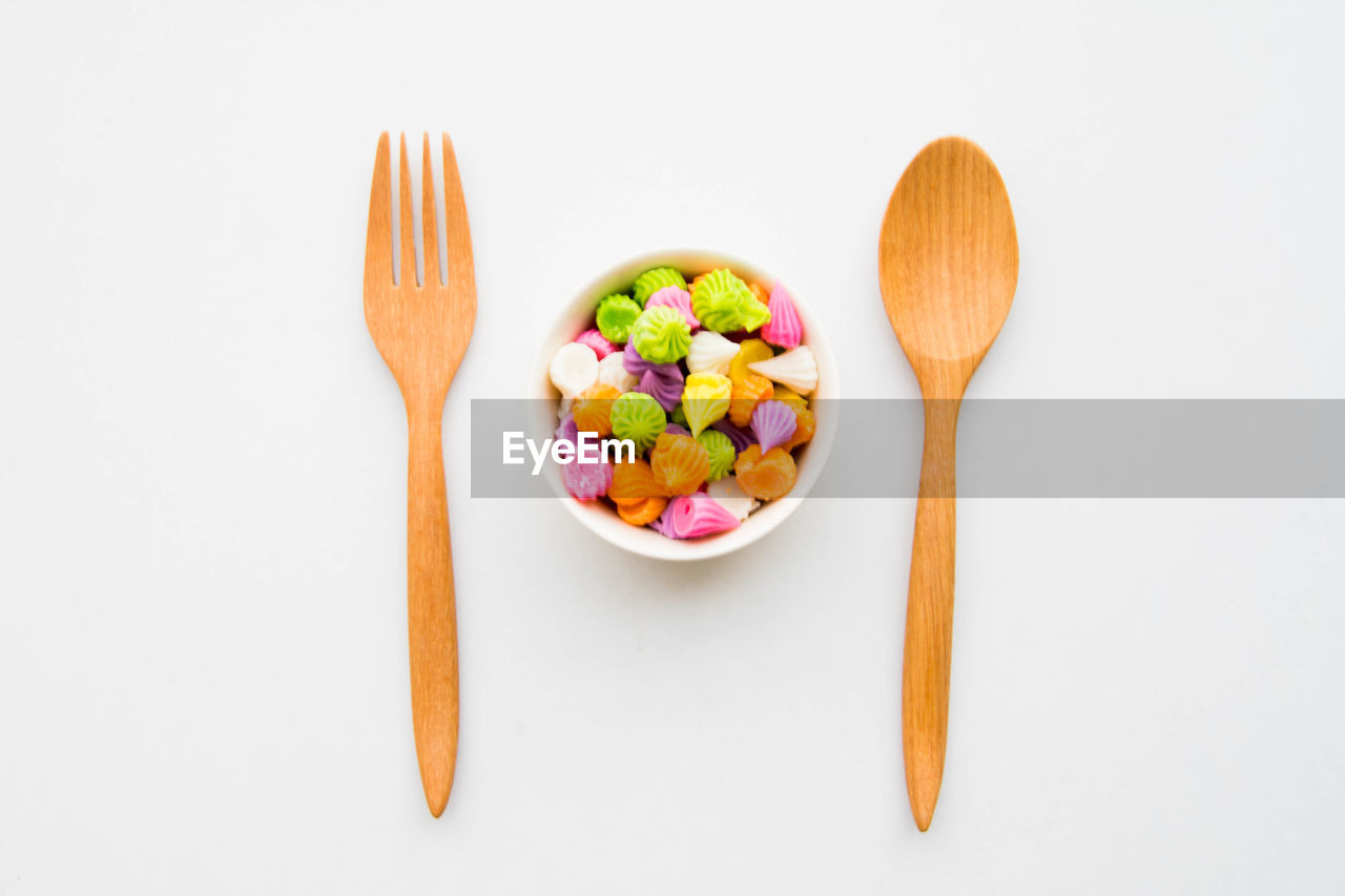 Directly Above View Of Colorful Candies In Bowl By Wooden Spoon And Fork On White Background