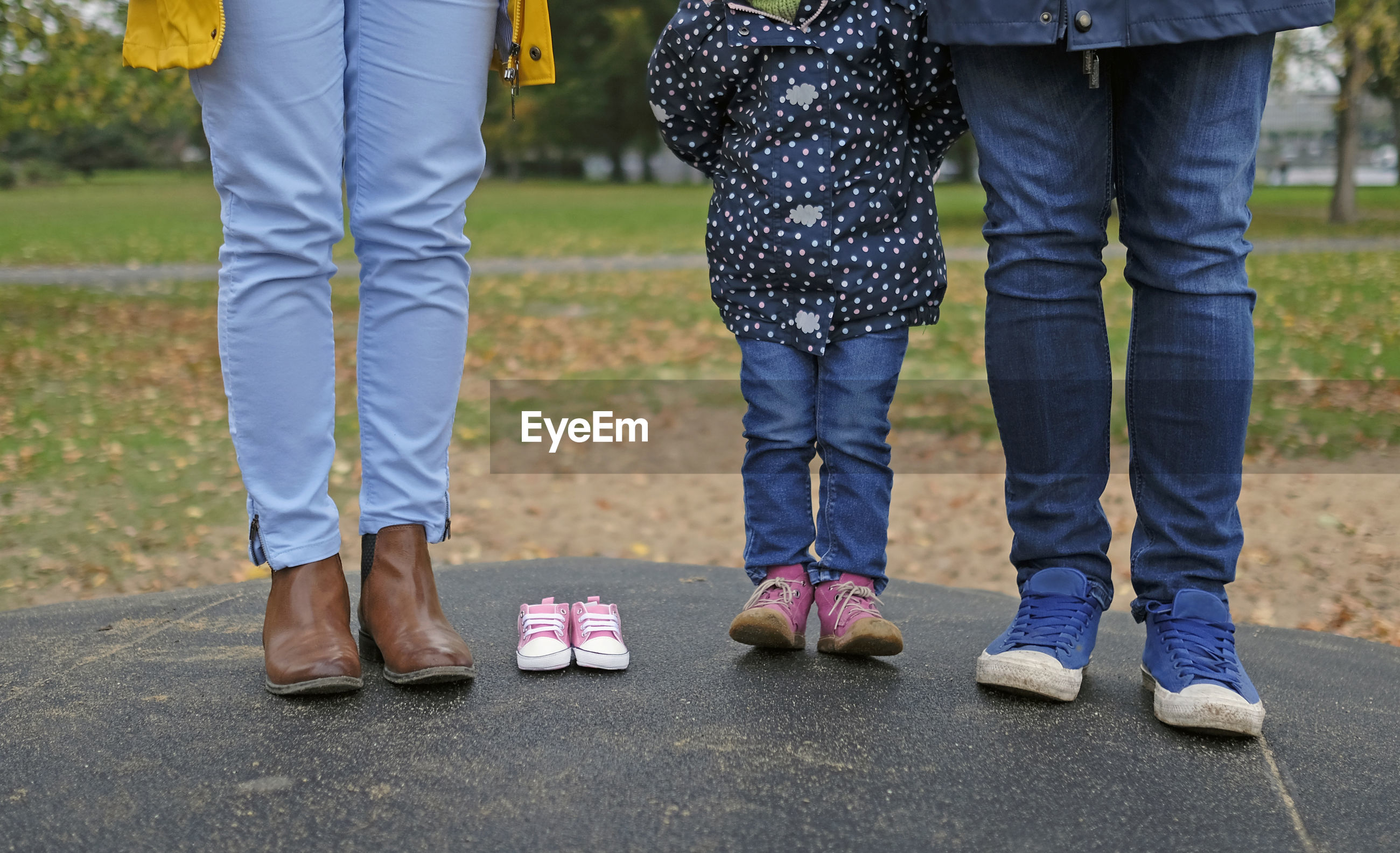 Low section of family standing by baby booties on land