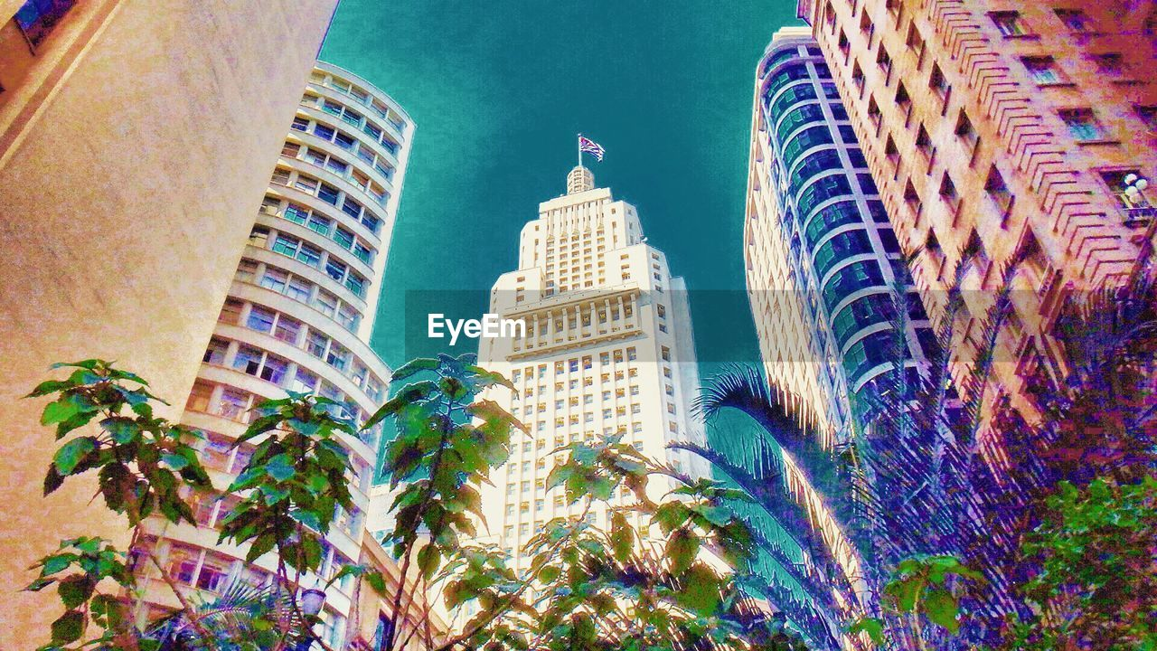 architecture, building exterior, built structure, low angle view, skyscraper, travel destinations, city, outdoors, growth, modern, plant, no people, palm tree, tree, day, sky, illuminated, cityscape