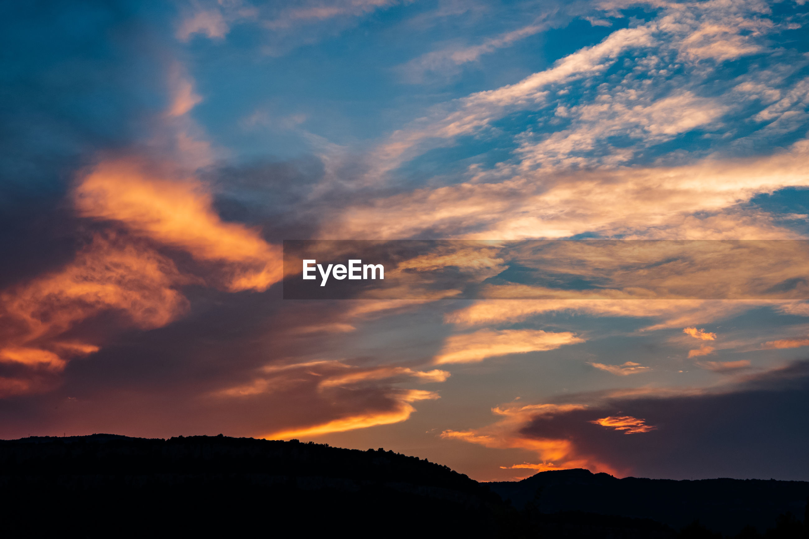 LOW ANGLE VIEW OF DRAMATIC SKY OVER SILHOUETTE MOUNTAINS