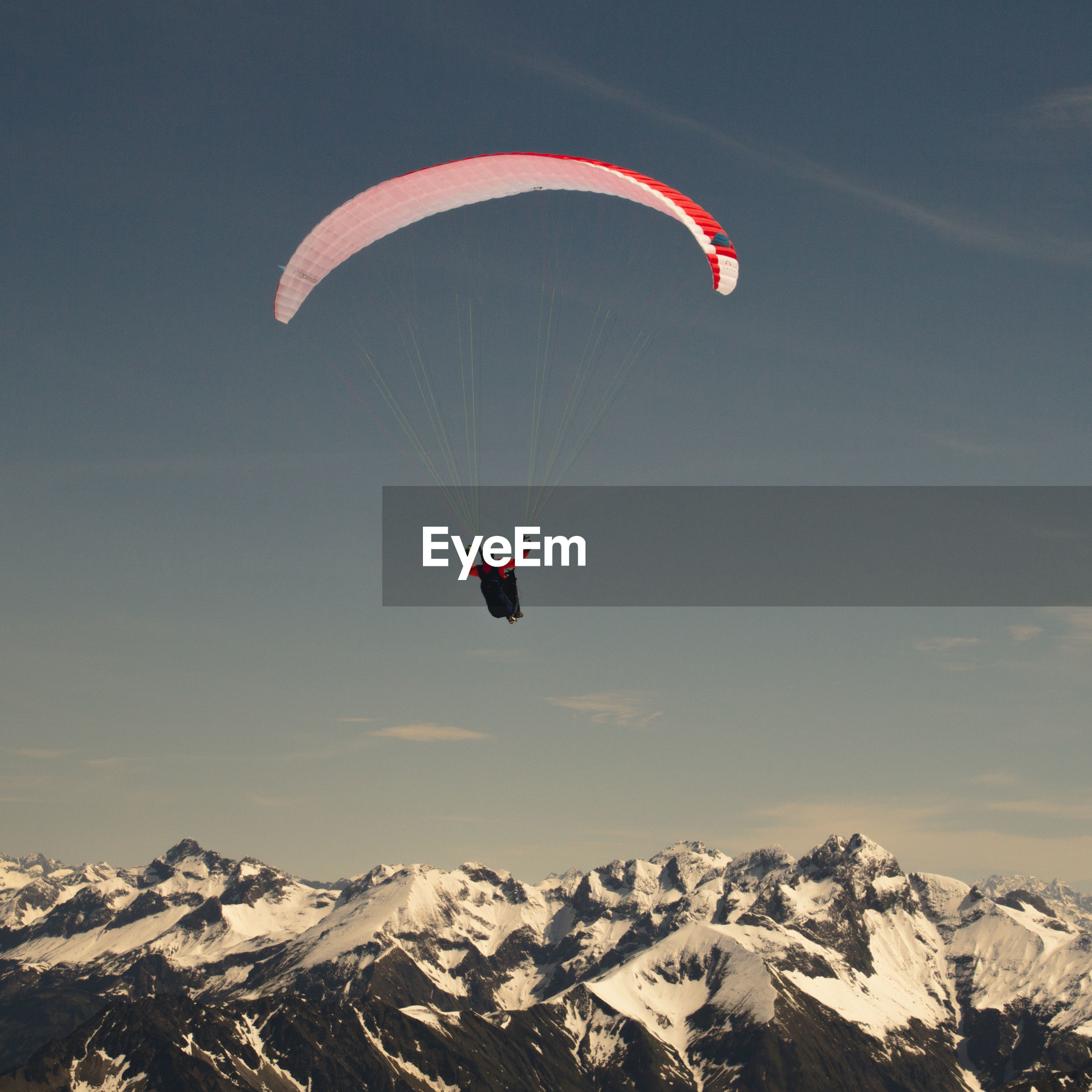 Low angle view of man parachuting above snowcapped mountains