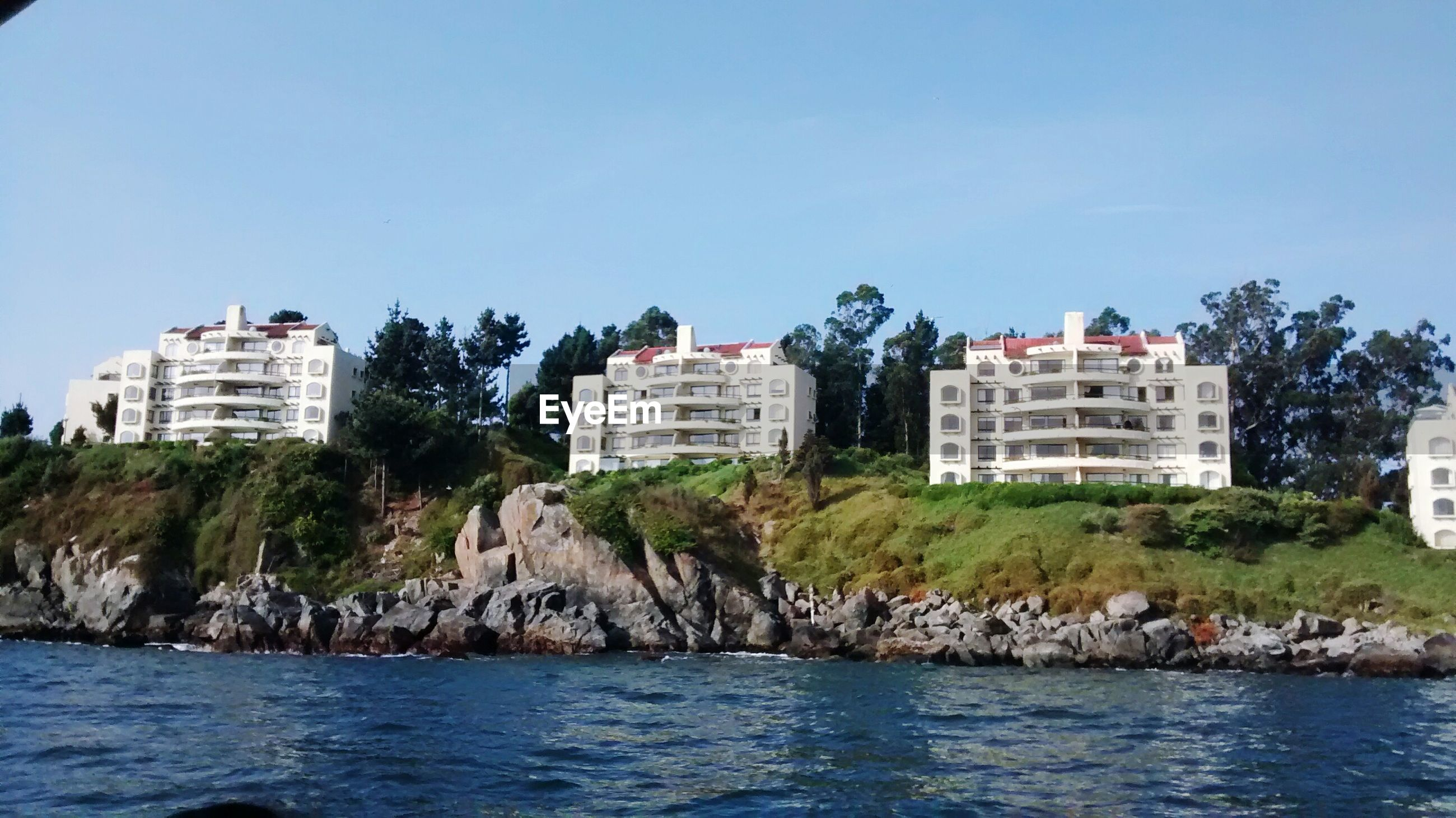 building exterior, architecture, water, built structure, waterfront, clear sky, tree, copy space, sea, blue, sky, house, rock - object, river, residential building, nature, day, rippled, residential structure, outdoors
