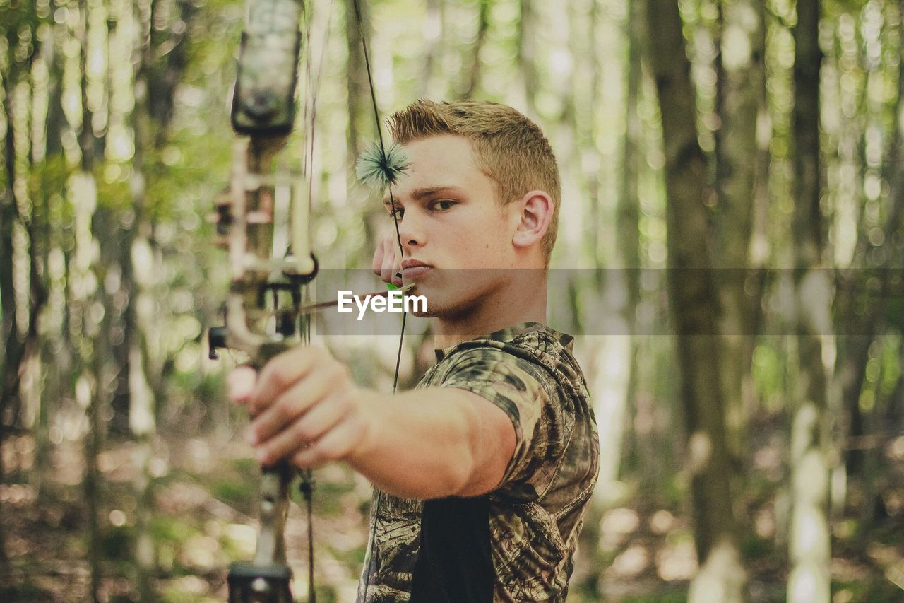 Confident Man Aiming With Bow And Arrow At Forest
