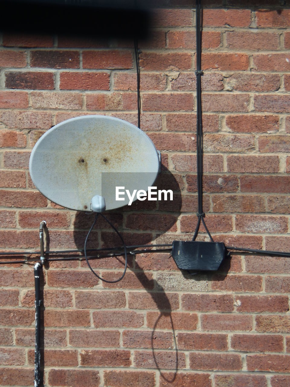 Satellite Dish And Cables On Brick Wall