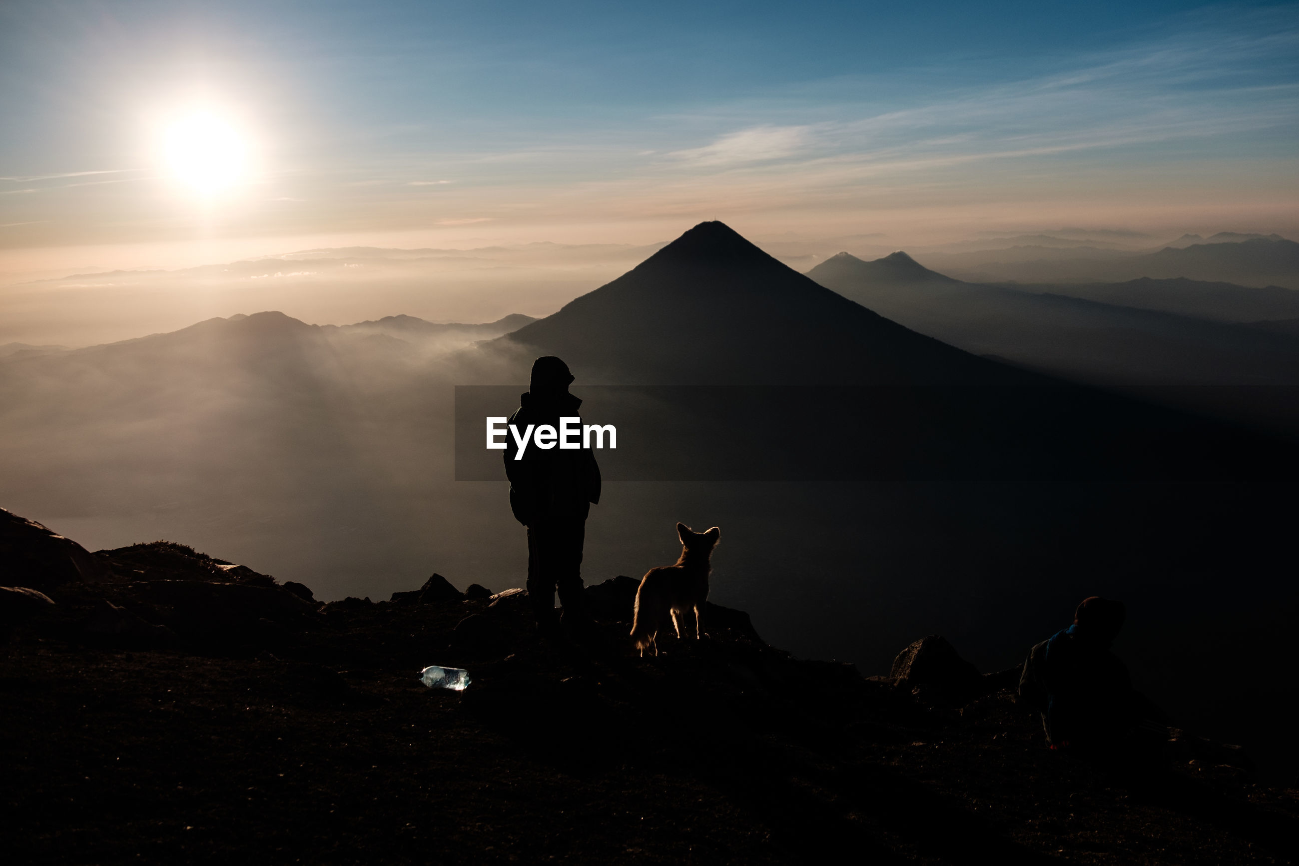 Silhouette people with dog on mountain range against sky