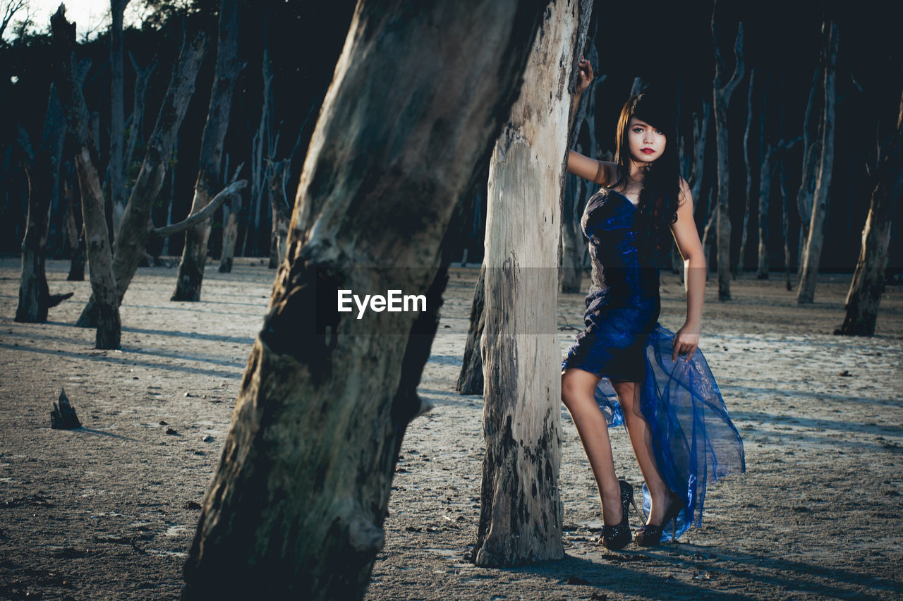 Full length portrait of beautiful fashion model standing by trees in forest