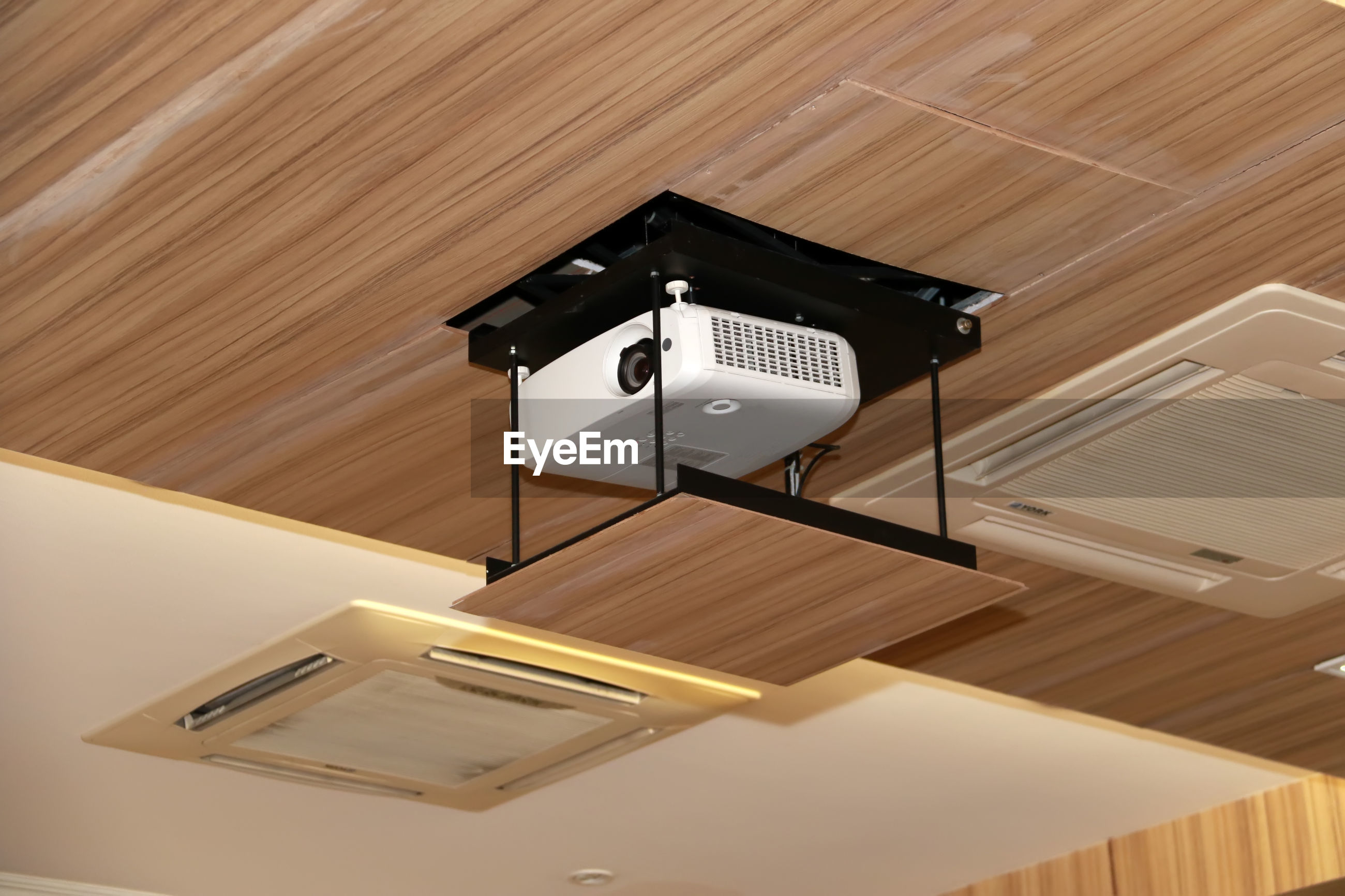 Low angle view of projection equipment attached to ceiling in conference room
