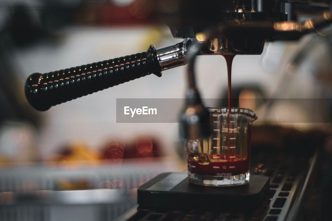 Close-up of coffee pouring in measuring cup at cafe