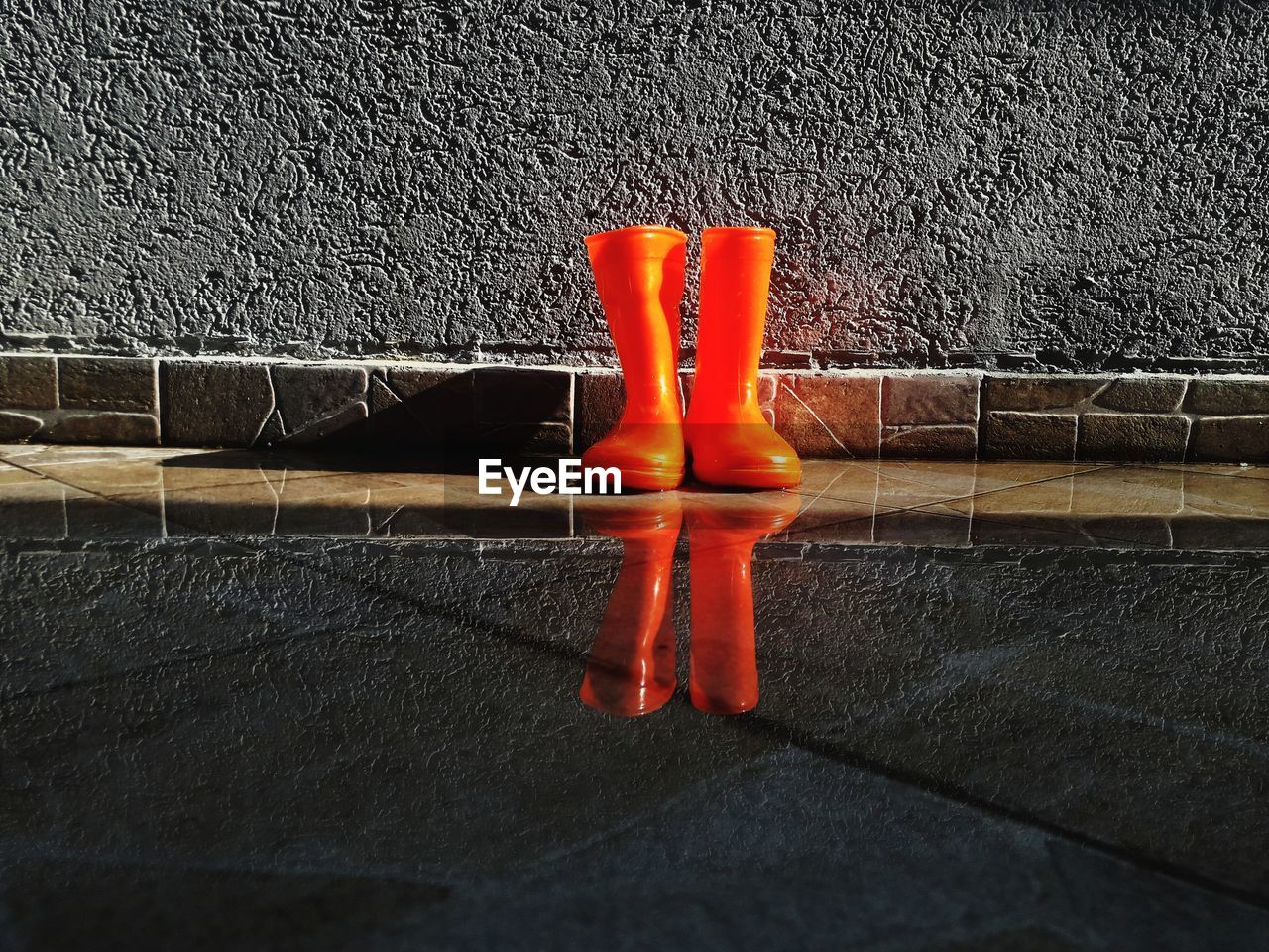 Orange Rubber Boots On Puddle Against Wall