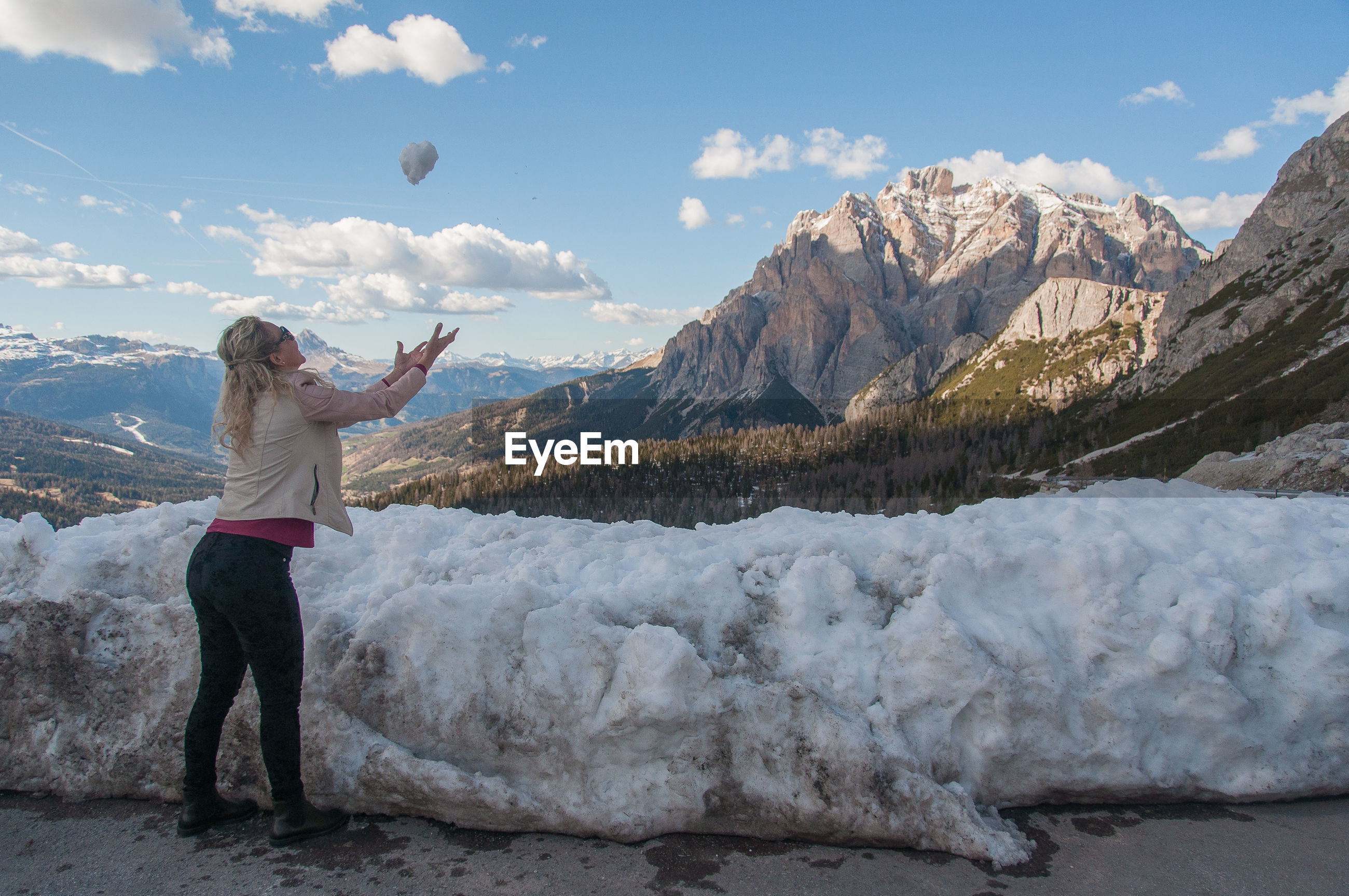 Side view of woman playing with snow on snowcapped mountains against sky