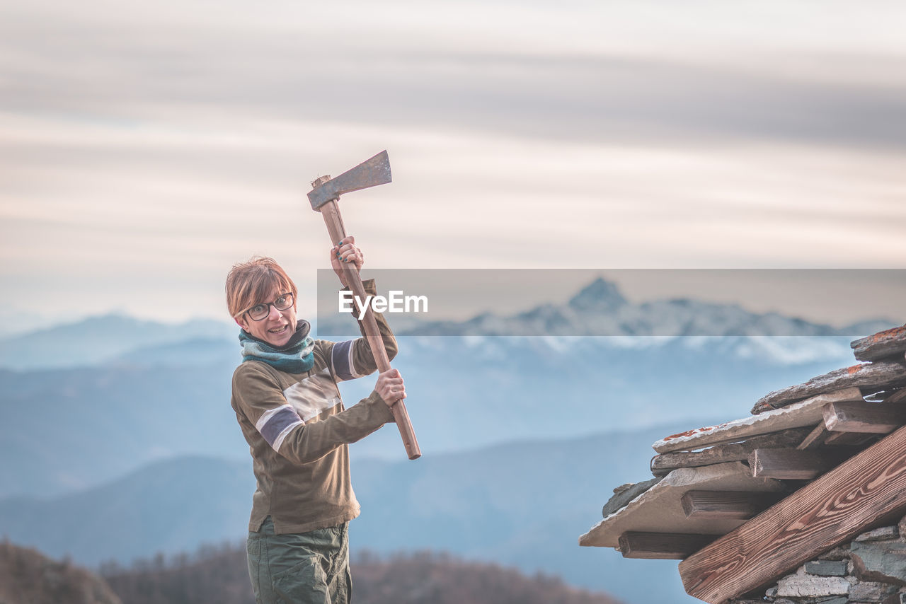 Portrait of angry woman holding axe against sky