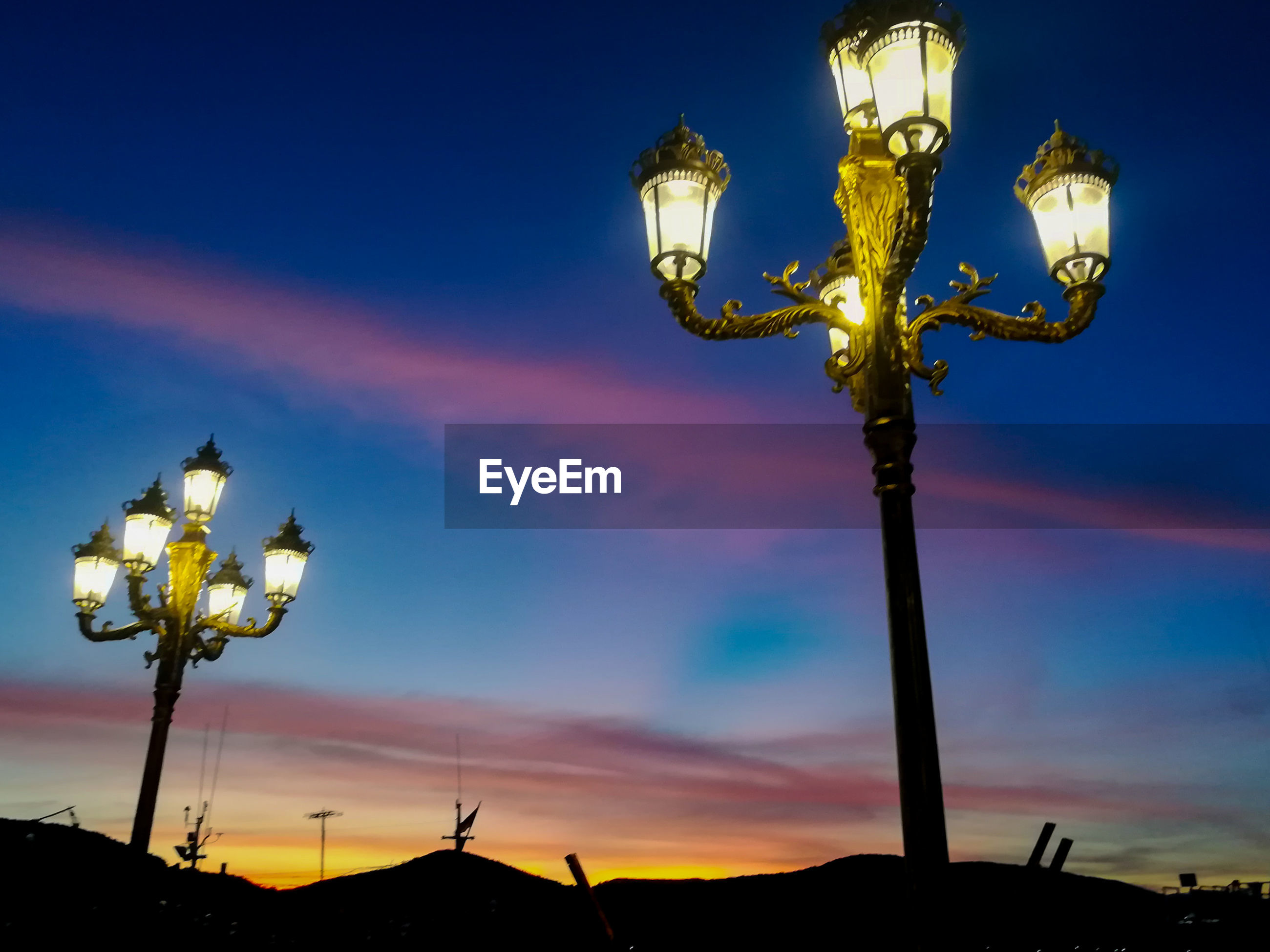 Low angle view of illuminated street light against sky at sunset