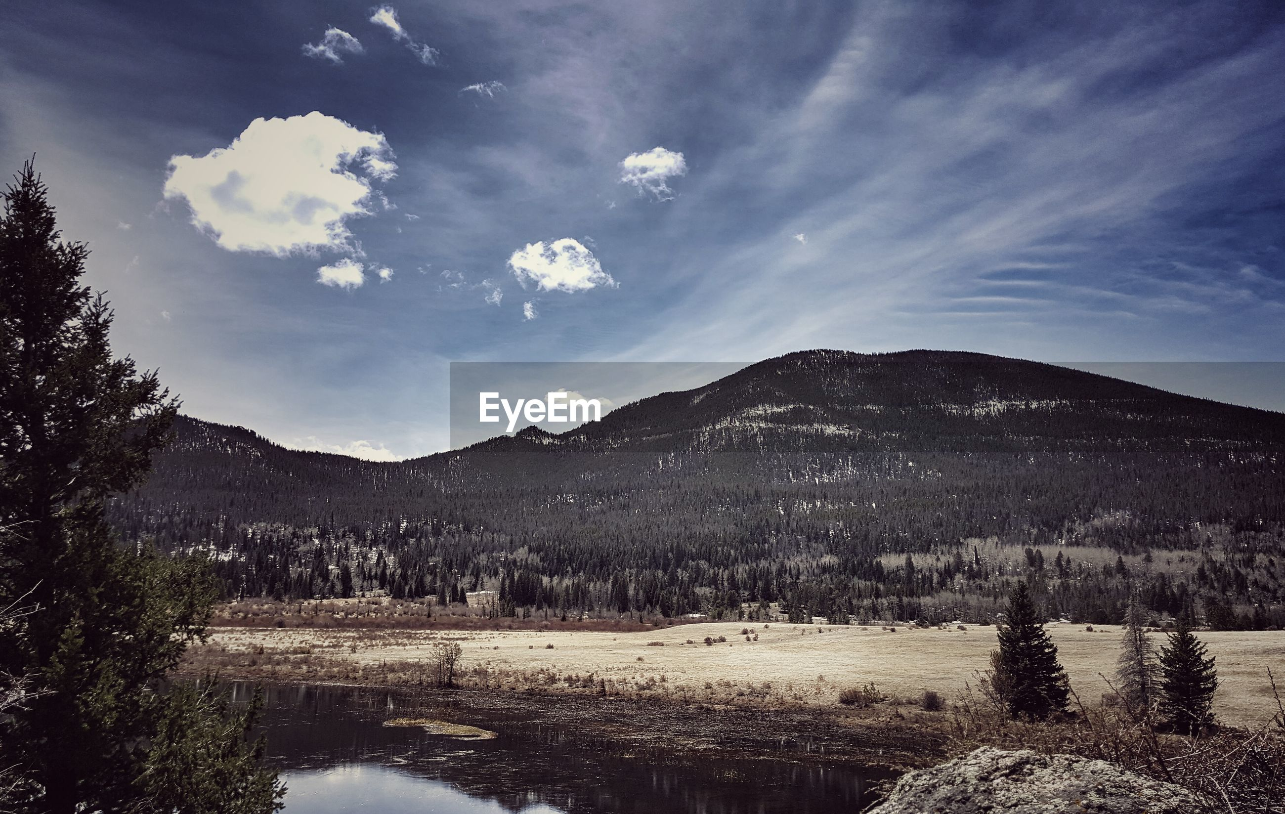 Scenic view of mountains by lake against blue sky