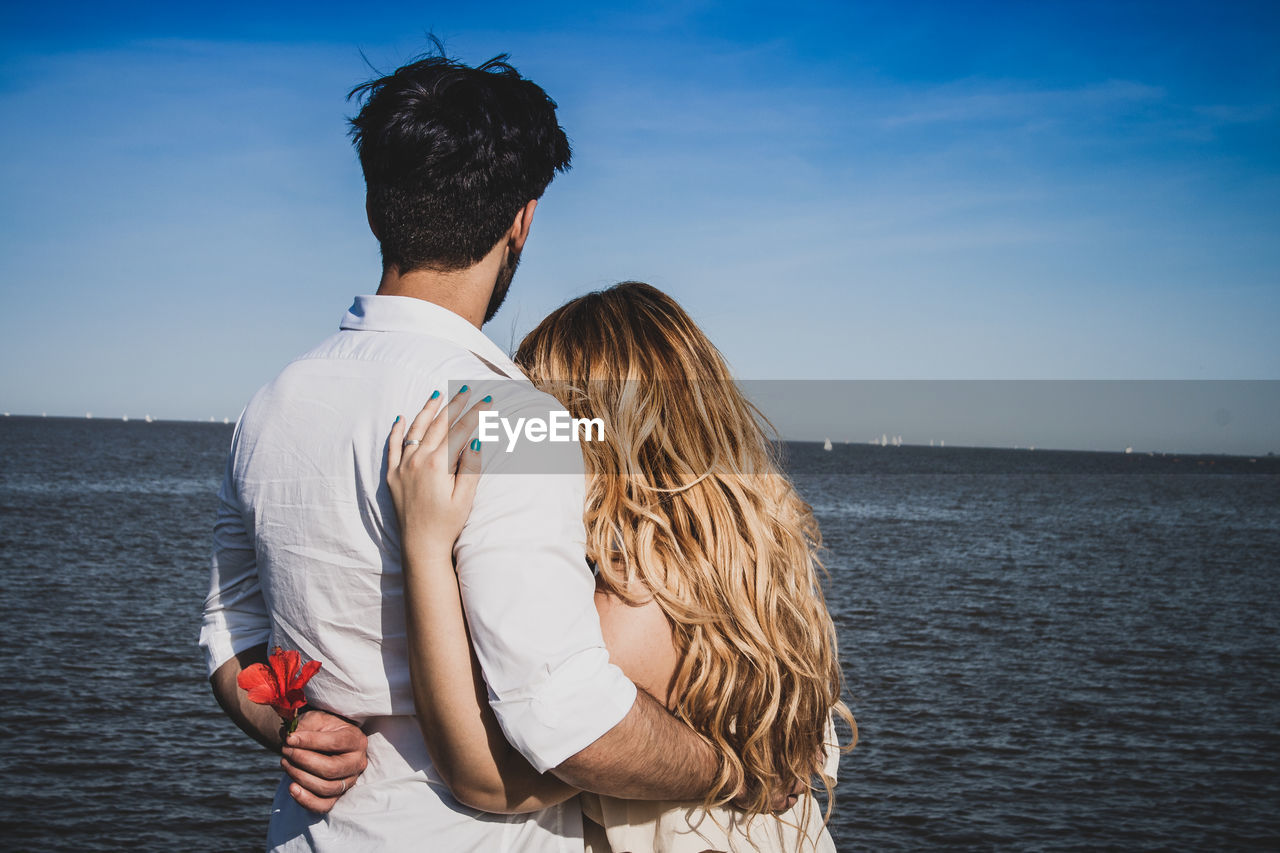 Rear view of couple with arm around standing by sea against sky