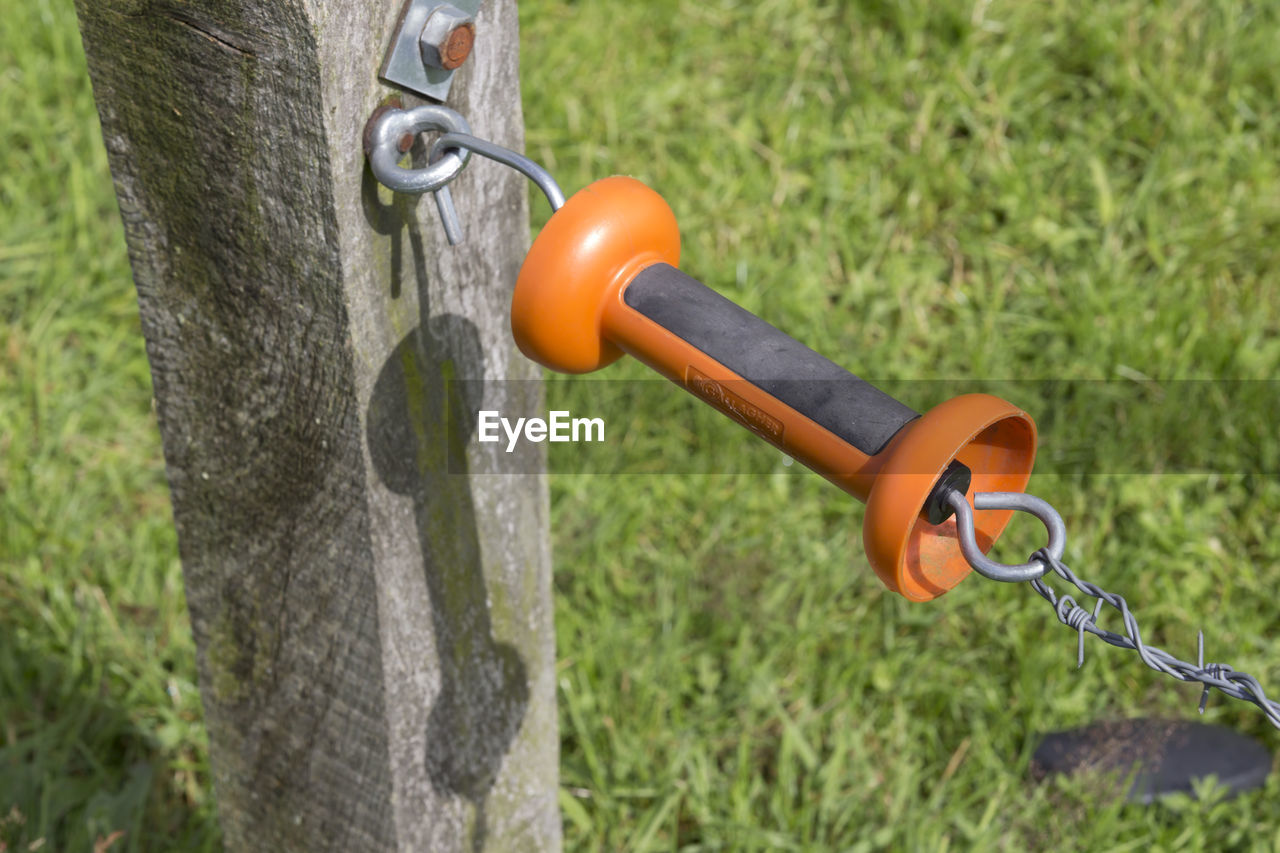 High Angle View Of Orange Handle Attached To Barbed Wire Fence On Grassy Field