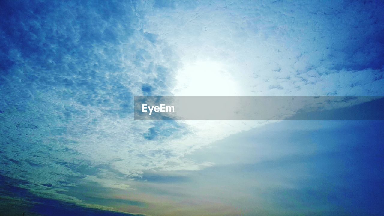 sky, sun, low angle view, nature, beauty in nature, sunbeam, blue, cloud - sky, scenics, day, sunlight, tranquil scene, outdoors, no people, tranquility, sky only, backgrounds