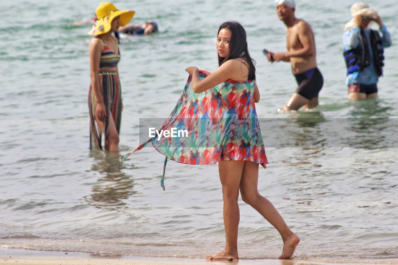 real people, water, sea, beach, leisure activity, standing, nature, day, focus on foreground, outdoors, lifestyles, one person, sand, waterfront, ankle deep in water, vacations, women, beauty in nature, young adult, adult, people