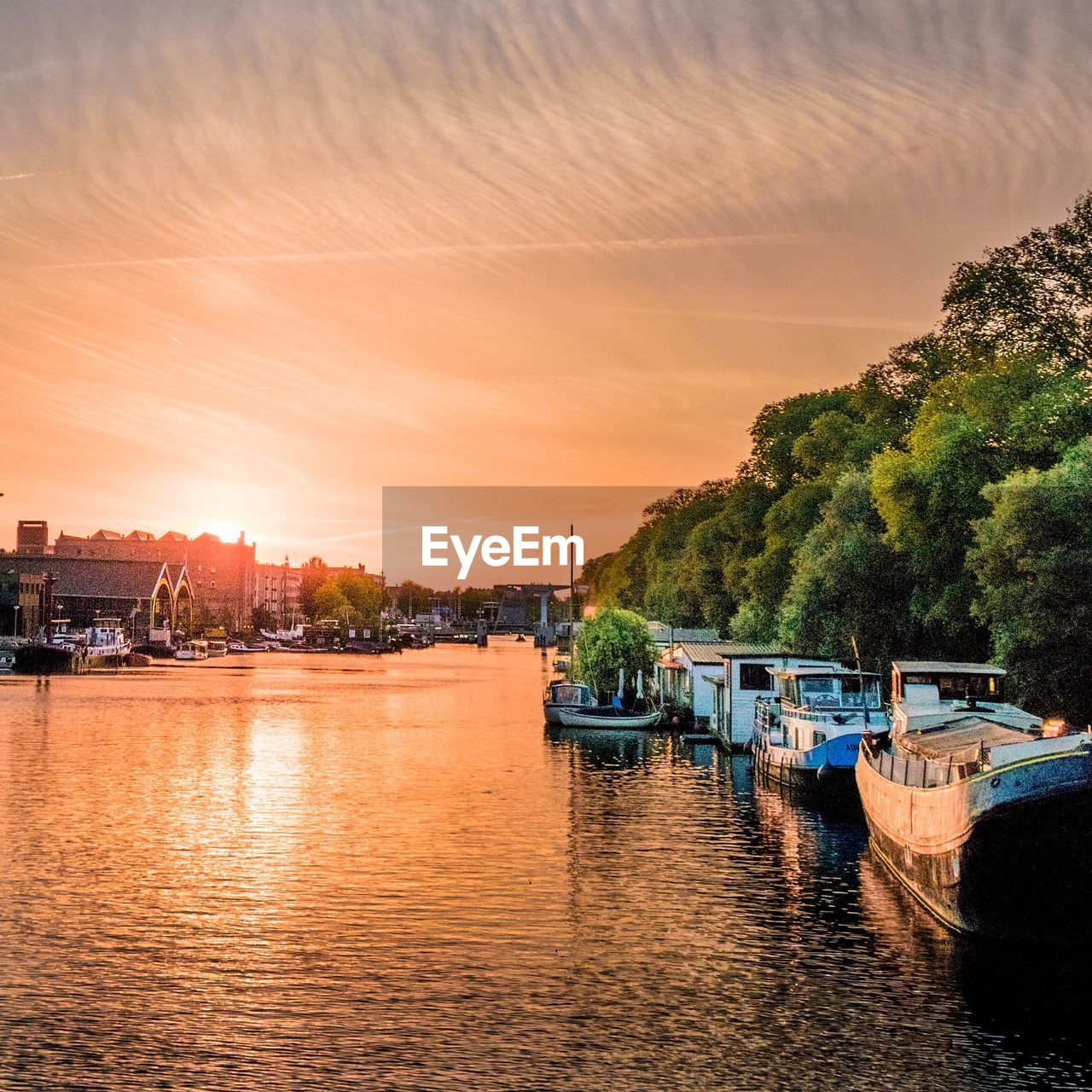 nautical vessel, river, transportation, tree, mode of transport, water, sunset, orange color, waterfront, built structure, moored, architecture, no people, reflection, sky, building exterior, nature, outdoors, beauty in nature, scenics, day
