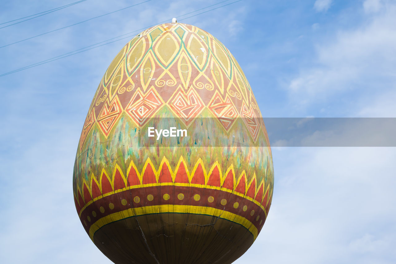 sky, low angle view, cloud - sky, day, pattern, nature, no people, sphere, outdoors, multi colored, architecture, built structure, building exterior, yellow, travel, tourism, art and craft, creativity, sunlight, balloon