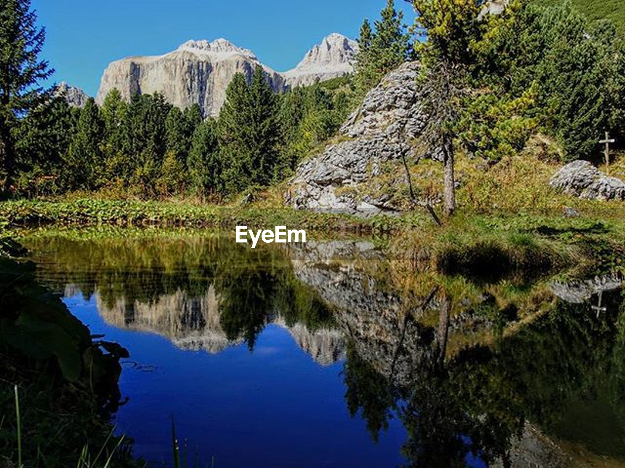 water, tranquil scene, tranquility, mountain, reflection, tree, scenics, beauty in nature, lake, nature, clear sky, idyllic, river, blue, non-urban scene, standing water, mountain range, rock - object, day, sunlight