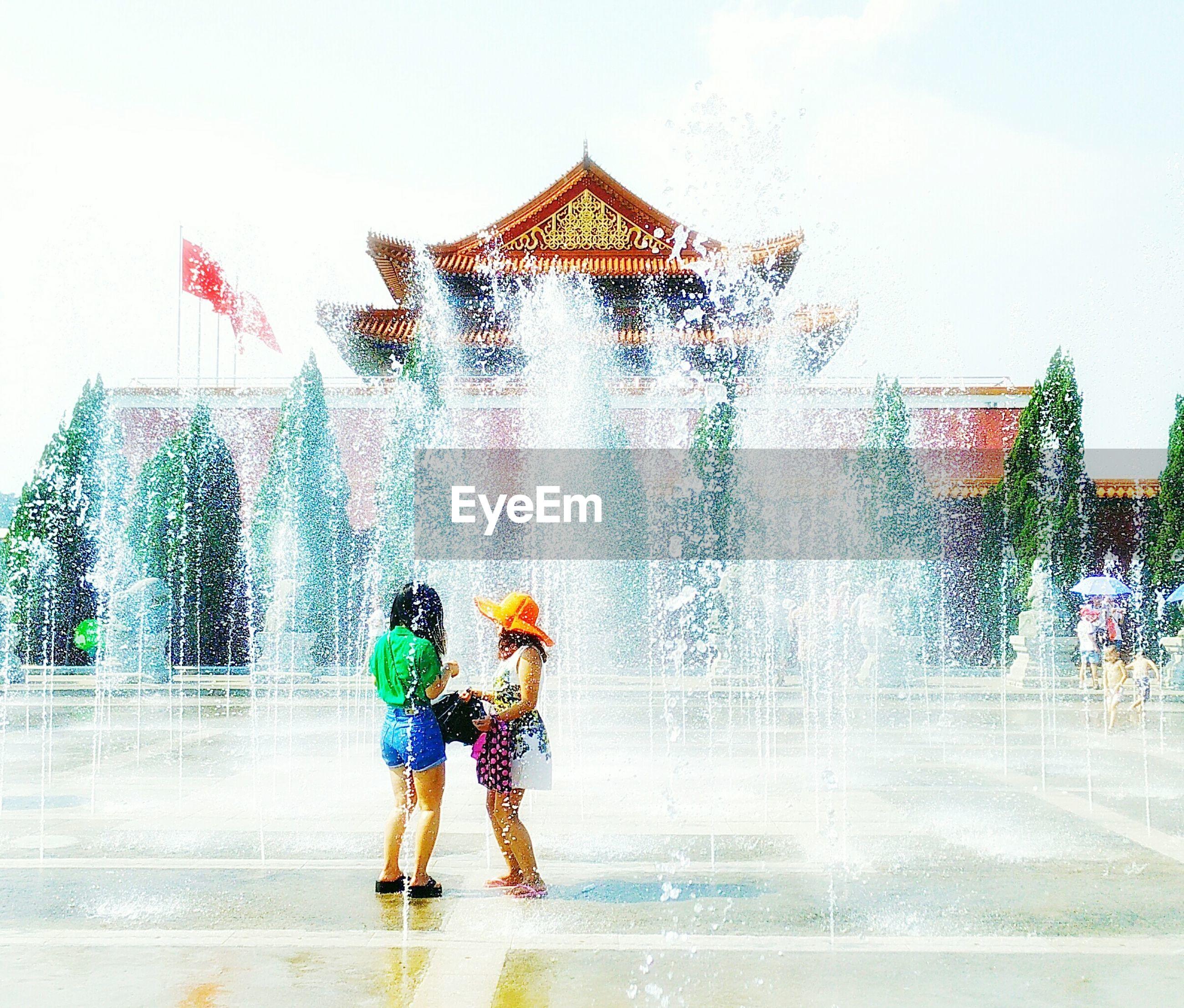 Full length of women standing against fountain