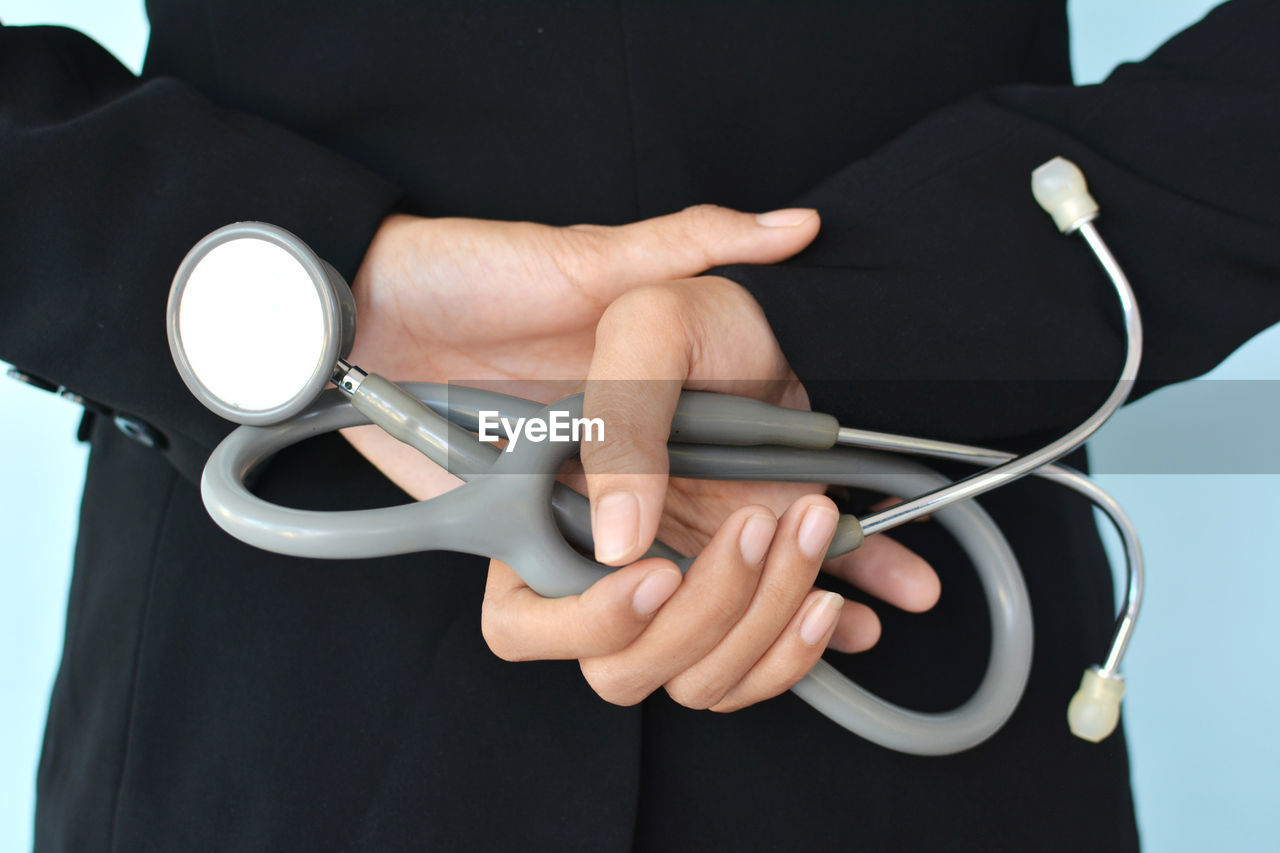 Midsection Of Doctor Holding Stethoscope While Standing Against Blue Background
