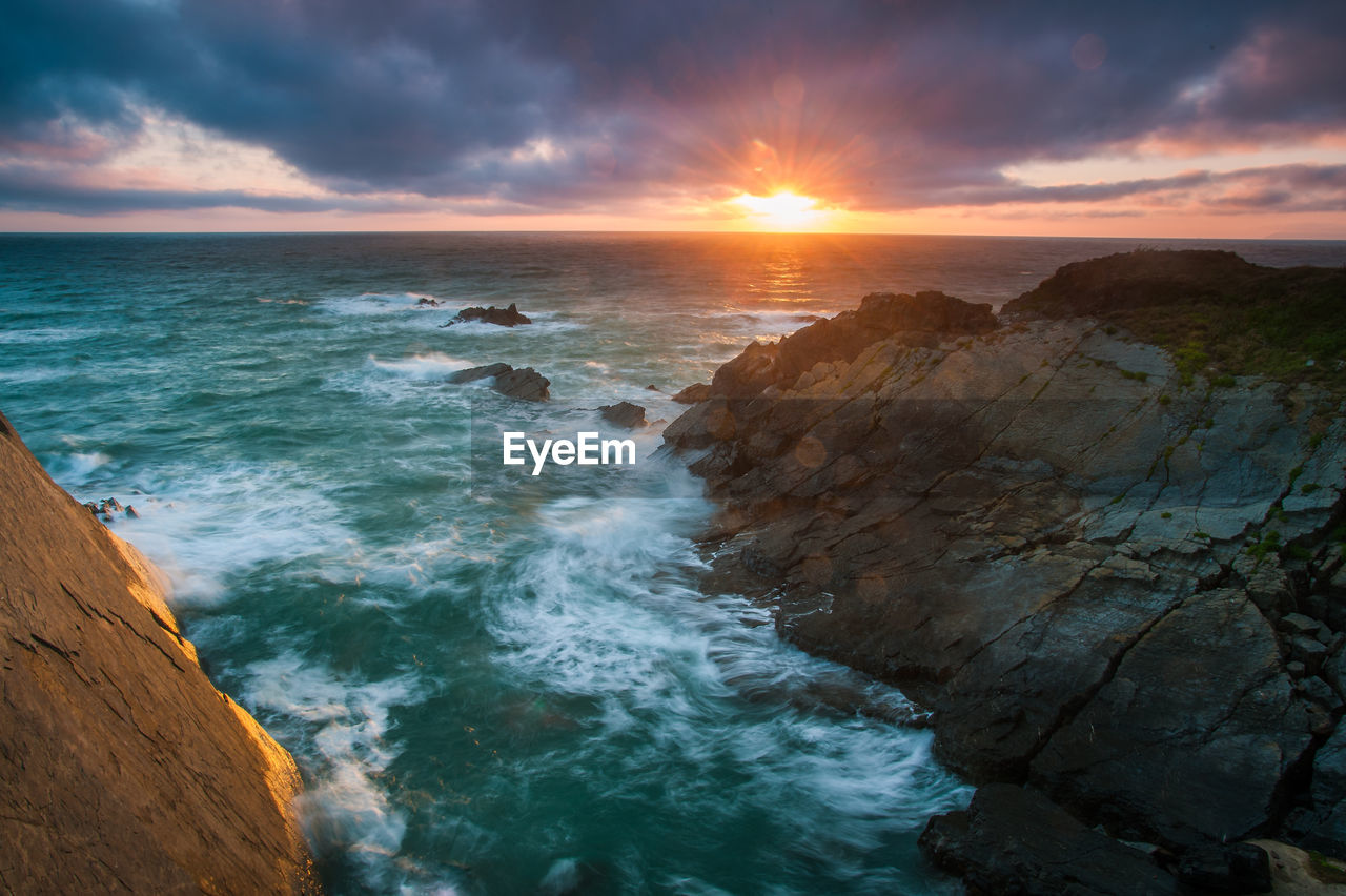 sea, water, beauty in nature, scenics - nature, sunset, sky, motion, rock, cloud - sky, solid, beach, land, rock - object, wave, horizon over water, nature, horizon, non-urban scene, tranquil scene, no people, sun, outdoors, power in nature, breaking